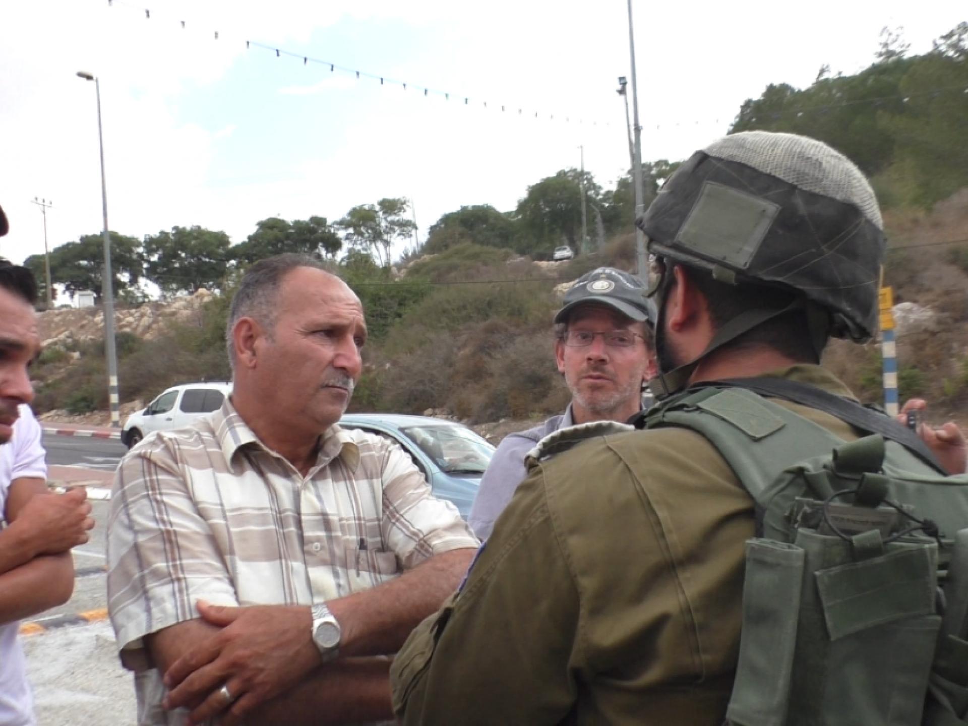 בעל השטח החקלאי ובניו דנים על הסדר כניסה לשטח עם המפקד הצבאי