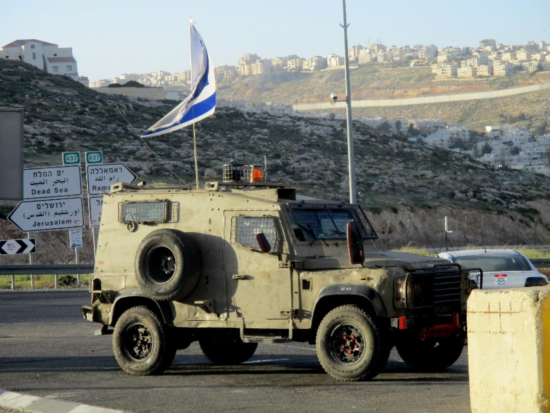 An army vehicle stands at the main entrance to Hizma
