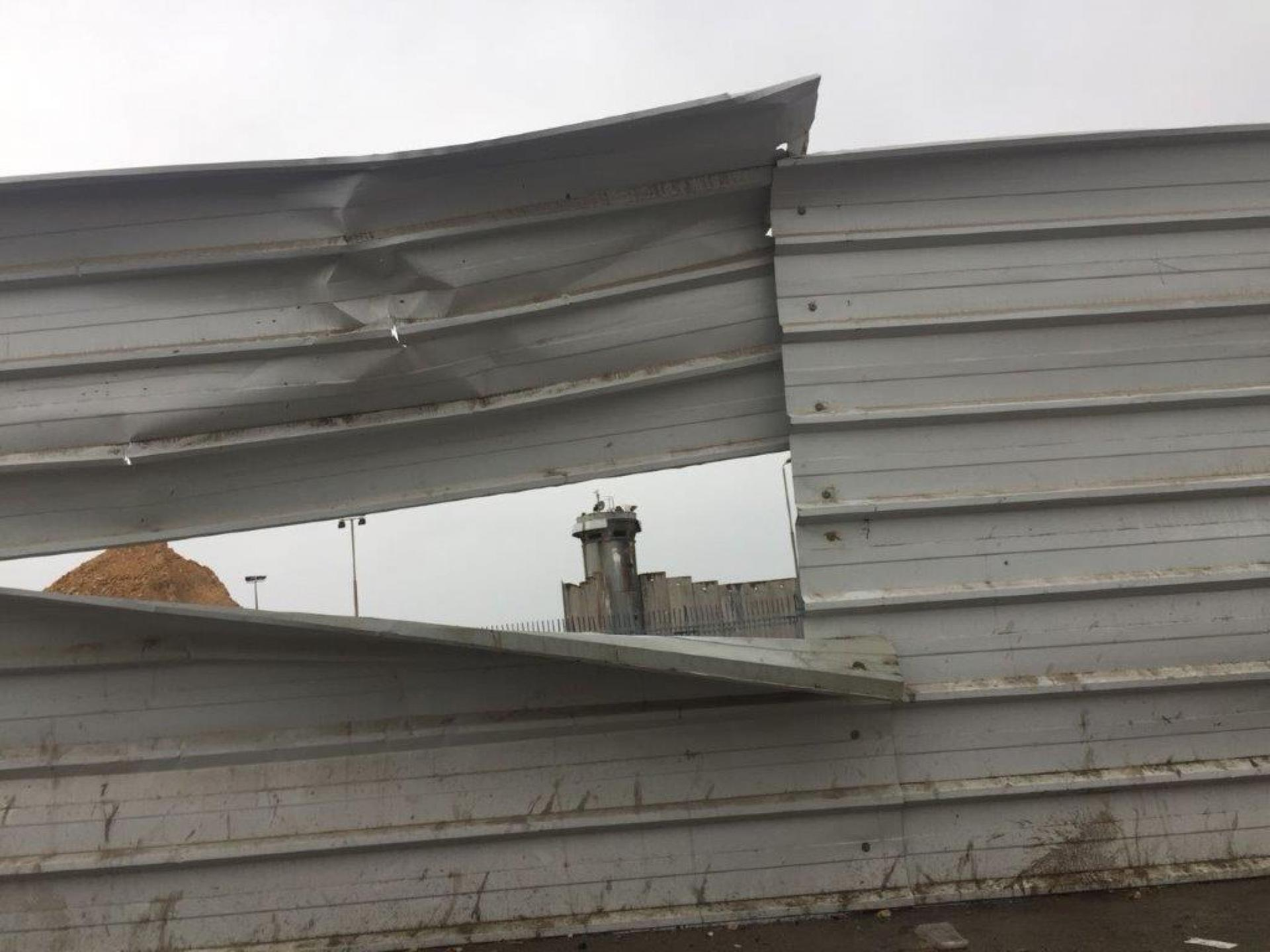 העדשה קלטה את אחד ממגדלי השמירה מציץ מבעד לגדר הפח