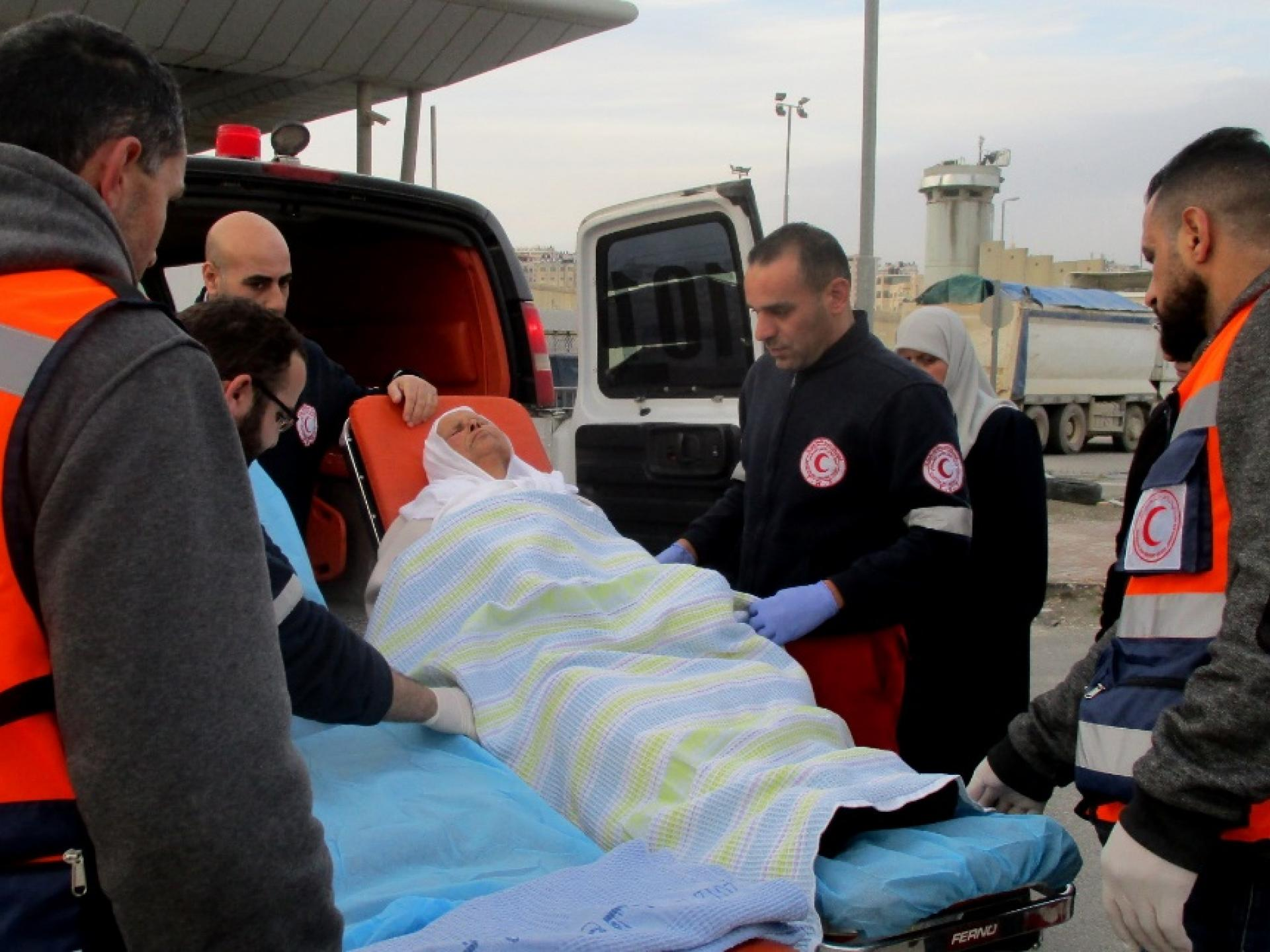 A woman cancer patient between the ambulances