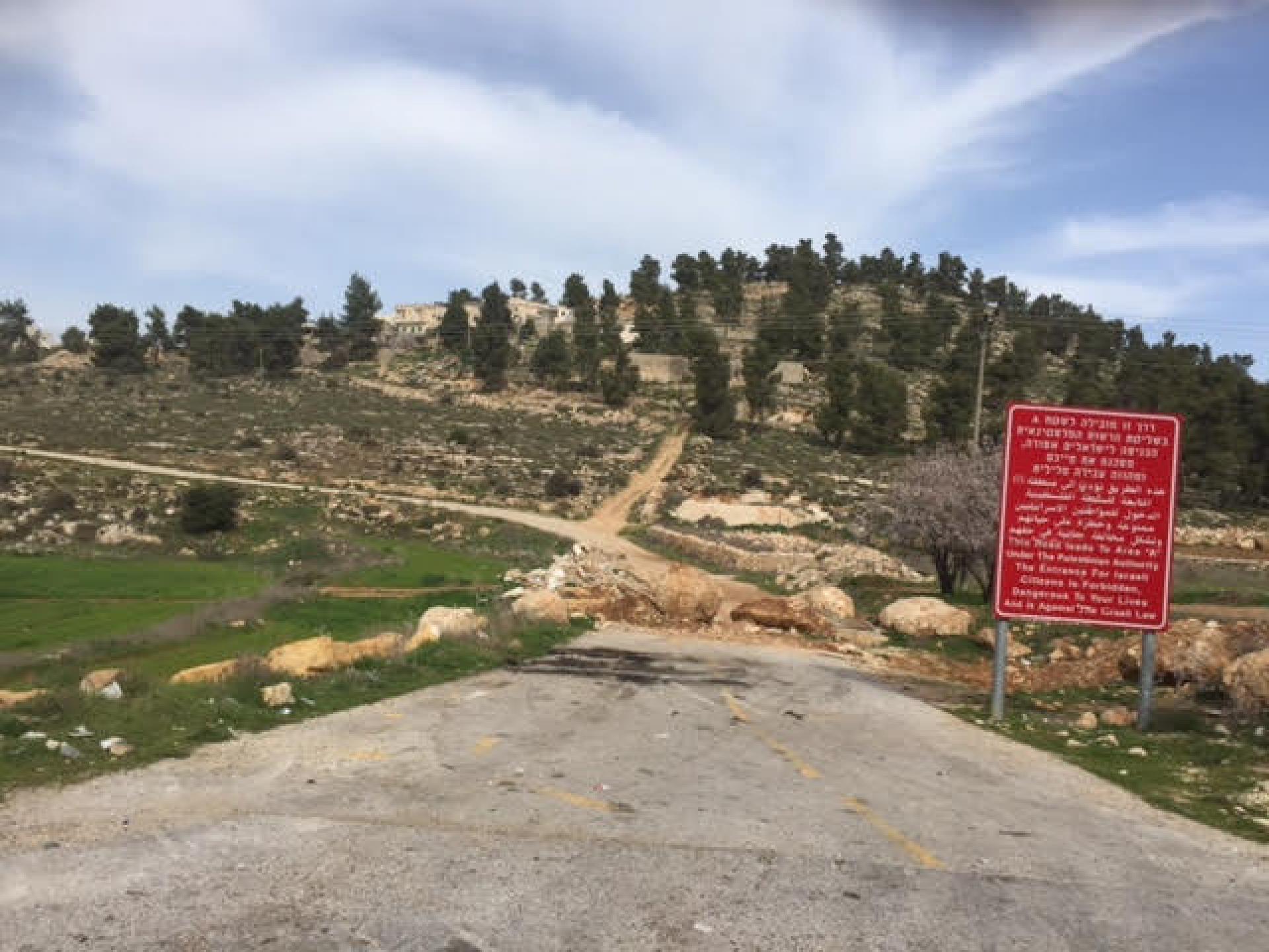 סוללה קטנה חוסמת כניסה ליישוב פלסטיני ולצידה שלט אדום המזהיר שזהו שטח A
