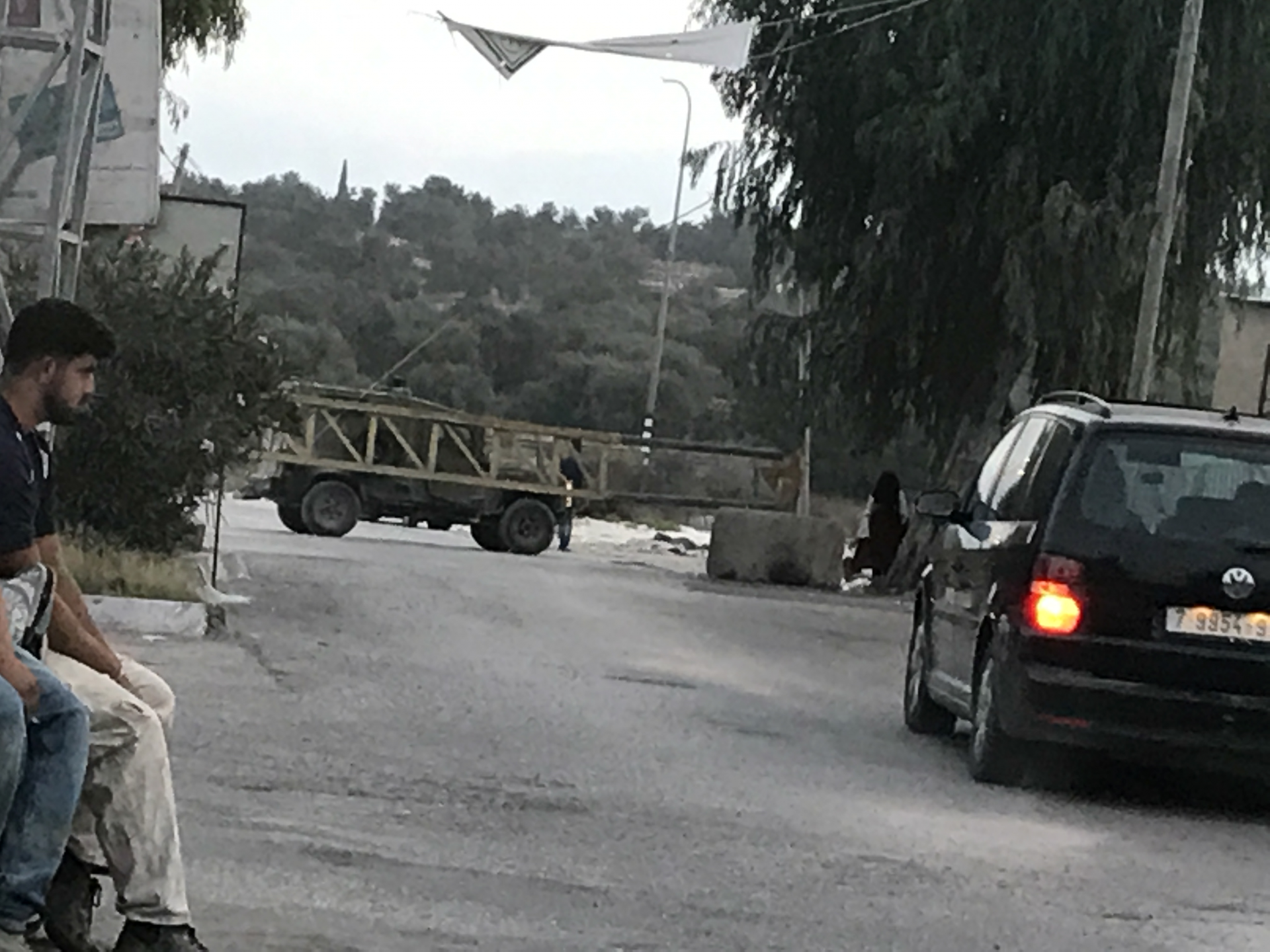 An arm's barrier blocks the entrance to Azzun