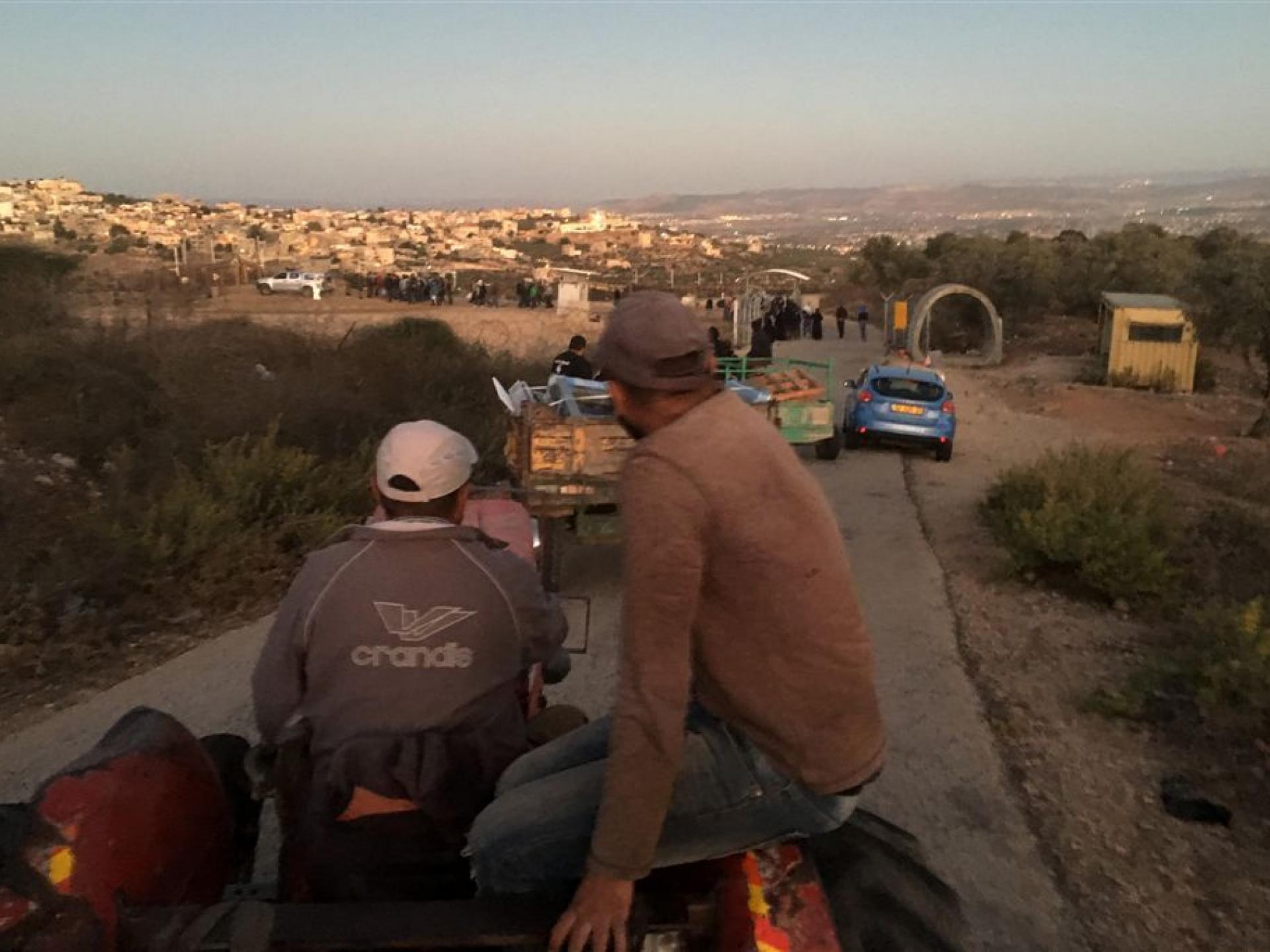 שיירה מעורבת עגלות ומכוניות לכיוון המחסום שנפתח
