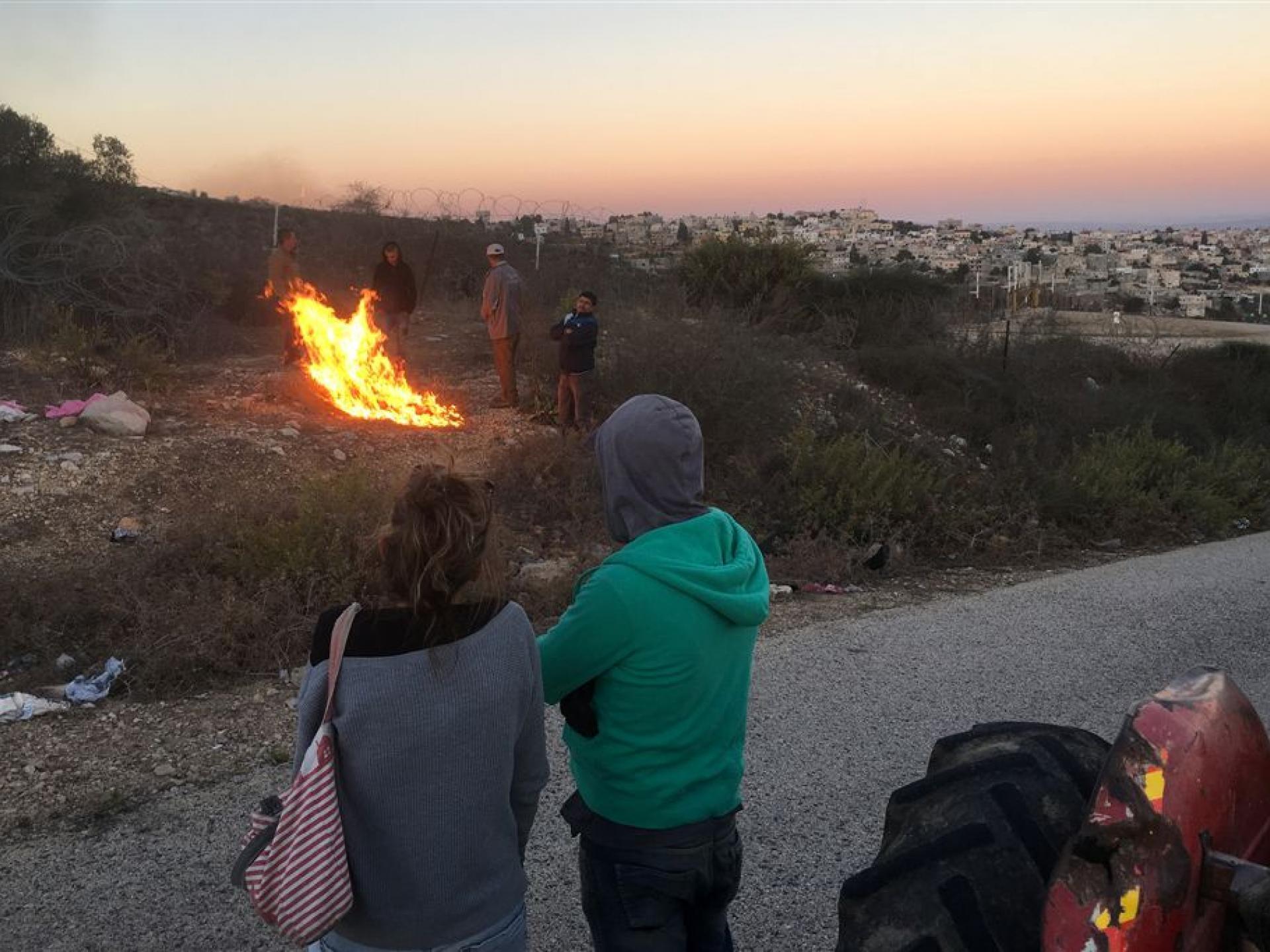 אנשים צופים במדורה שהדליקו בזמן ההמתנה