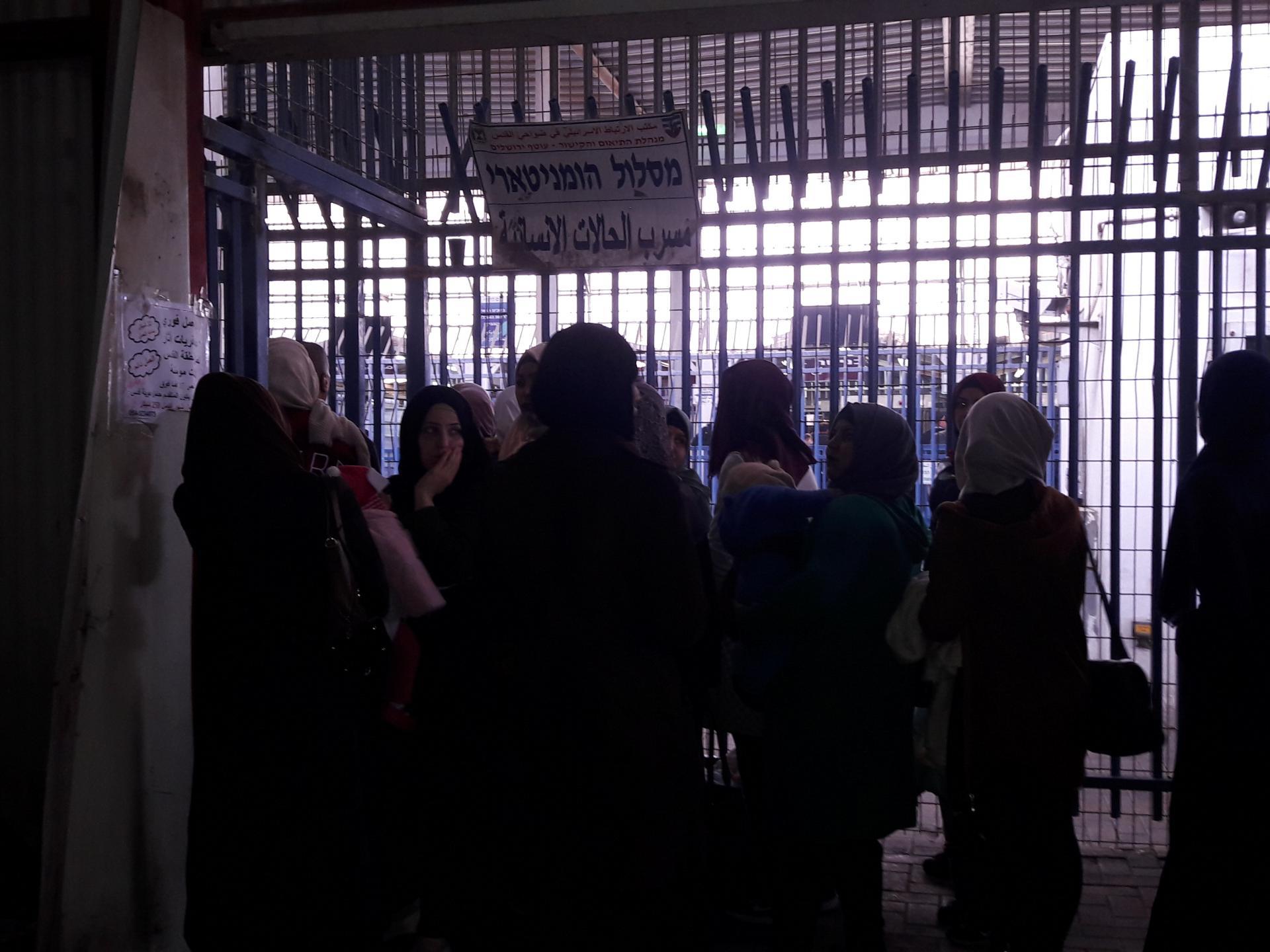 תור של נשים, חלקן עם ילדים בזרועותיהן, ממתינות לשווא ליד השער ההומניטרי