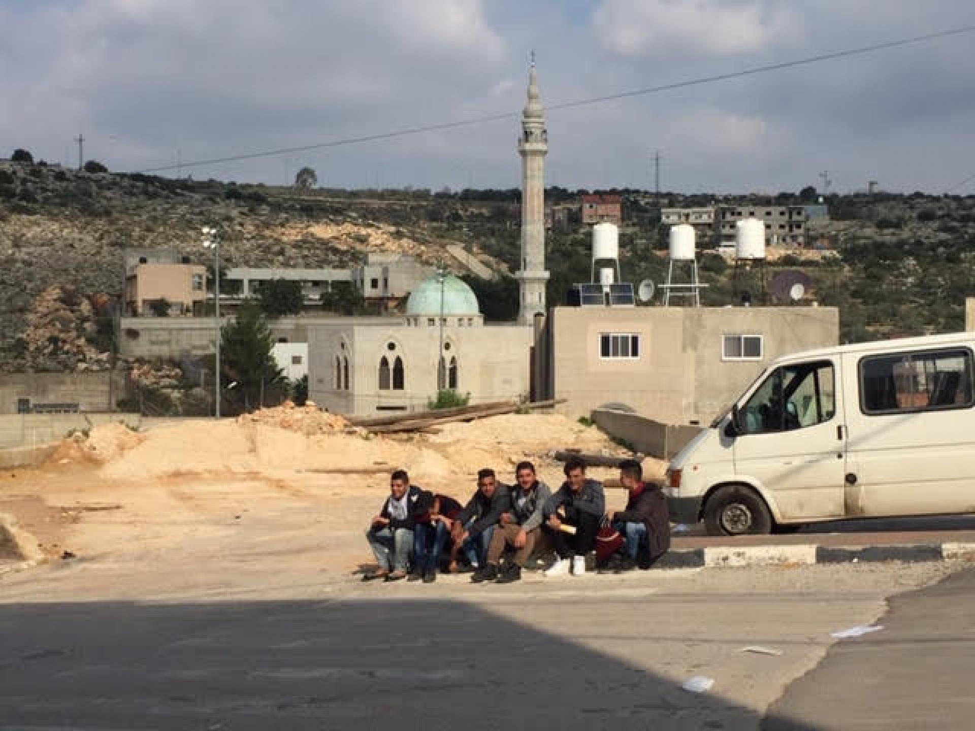 מול בנין המועצה קבוצת תלמידי תיכון בהפסקה מחיכים