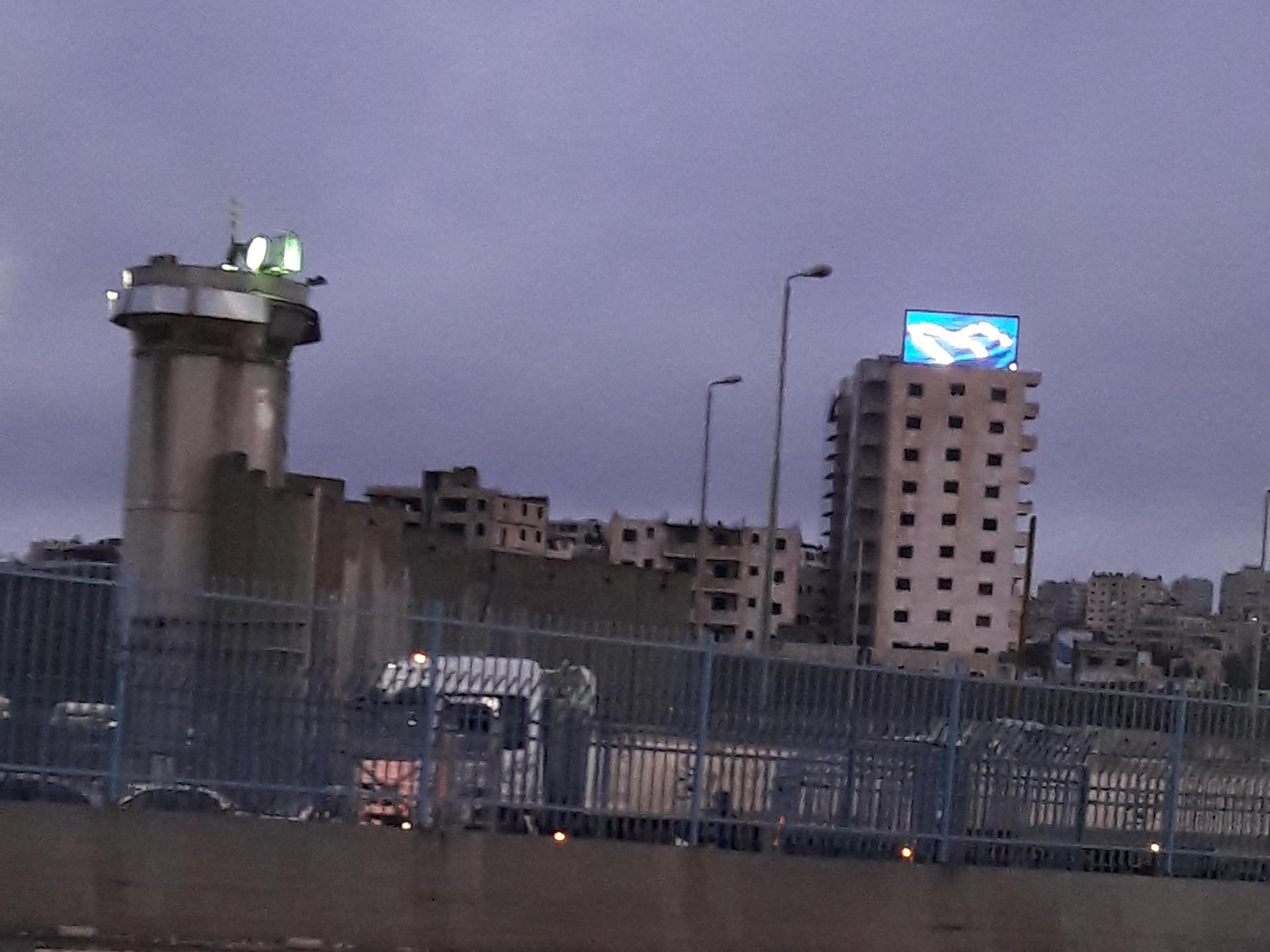 A neon sign, a wall and a watchtower