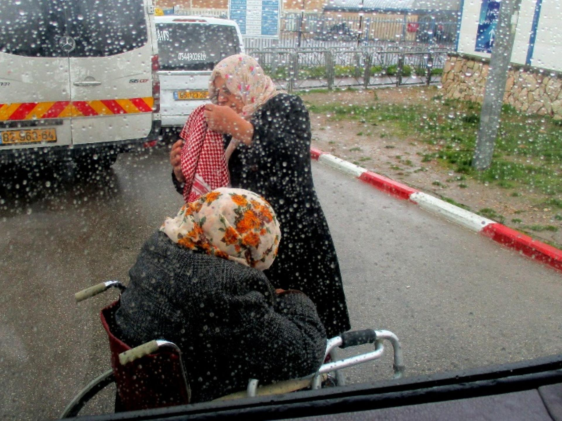 חולה בכסא נכים ליד רכב ההסעות המלא, בגשם