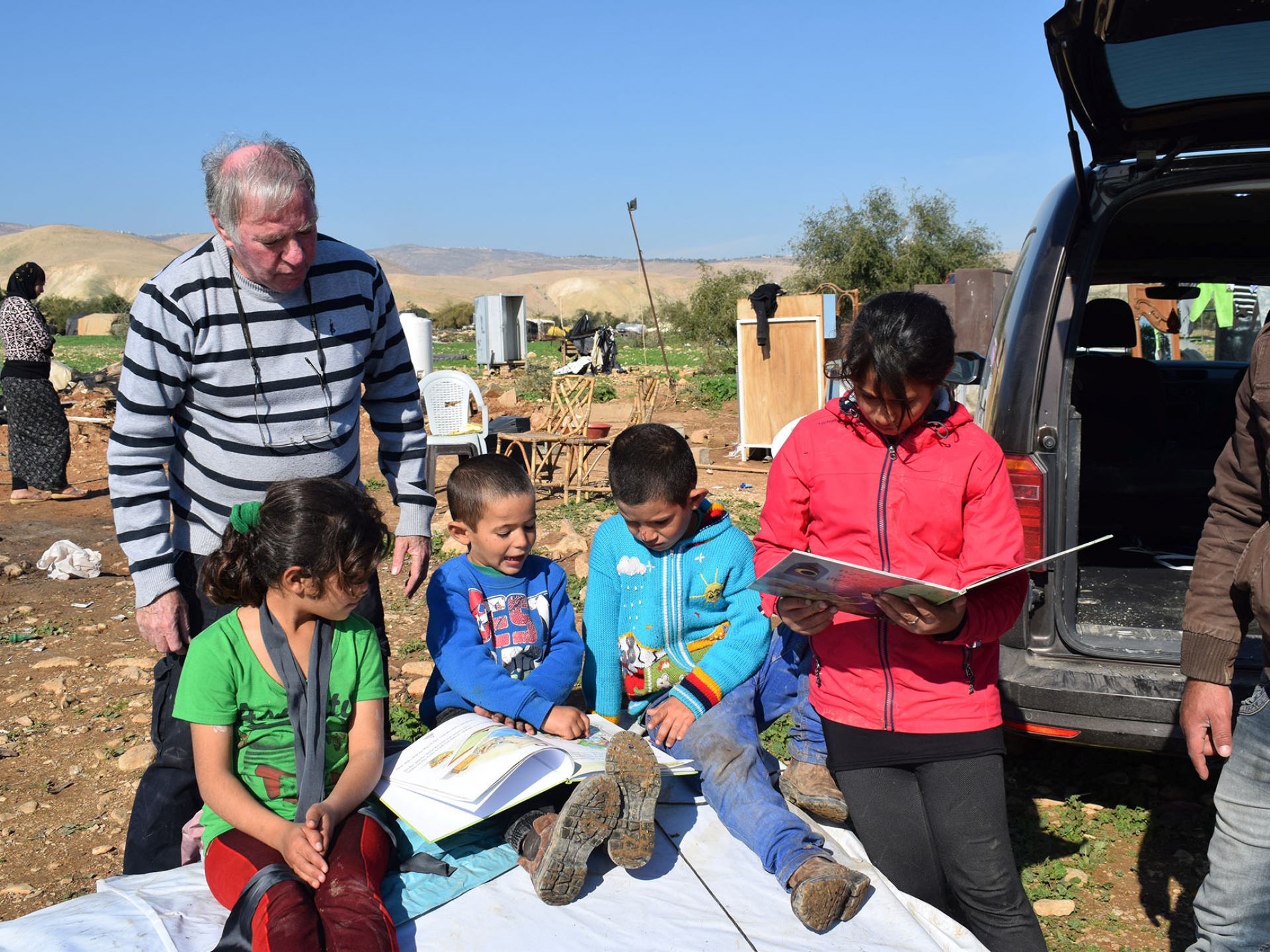 The family's children with illustrated books sitting on the still folded tent