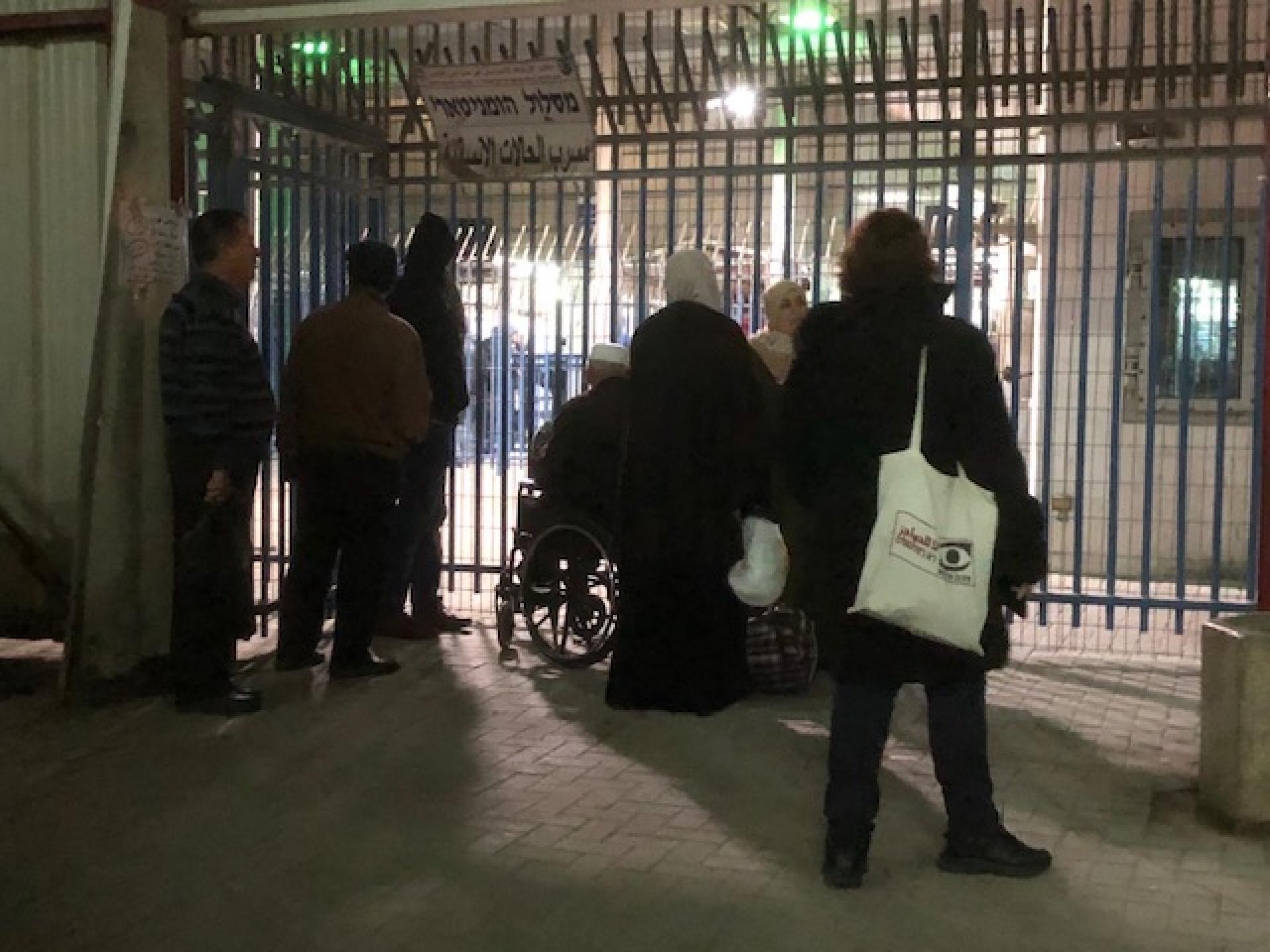 אדם בכסא גלגלים ממתין עם מלוויו לפני השער ההומניטרי