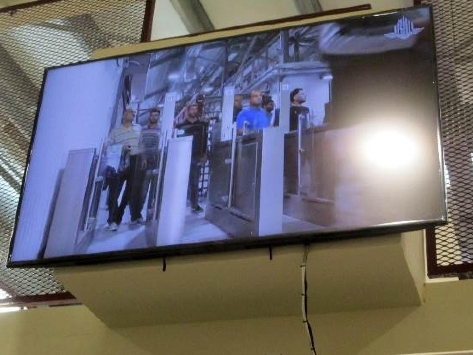 מסך ענק מקרין את הנעשה באולם, במחסום המשודרג.