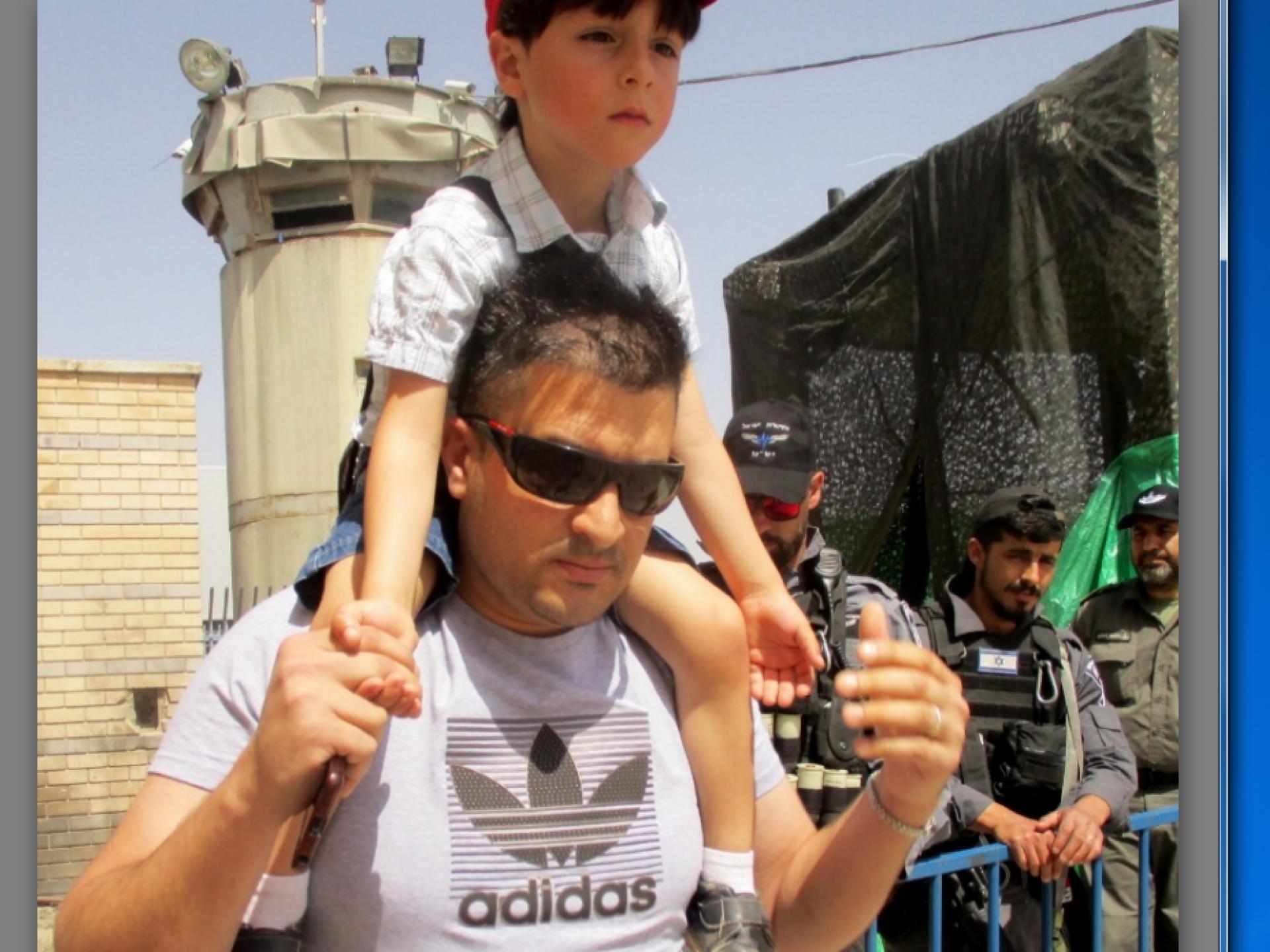 אב ובנו במחסום קלנדיה ביום שישי השני לחודש הרמדאן