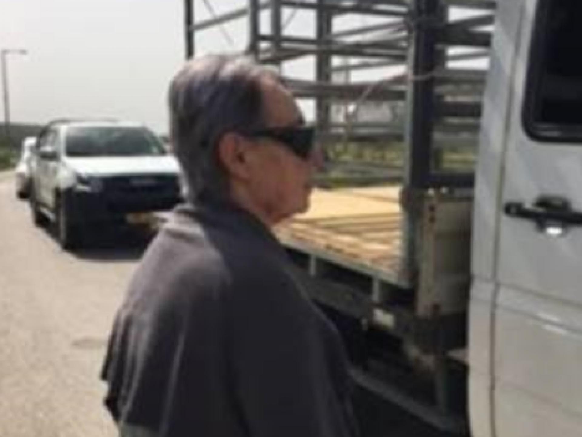 רואים בתמונה את חסידה משוחחת עם נהג משאית במגרש החניה של המחסום