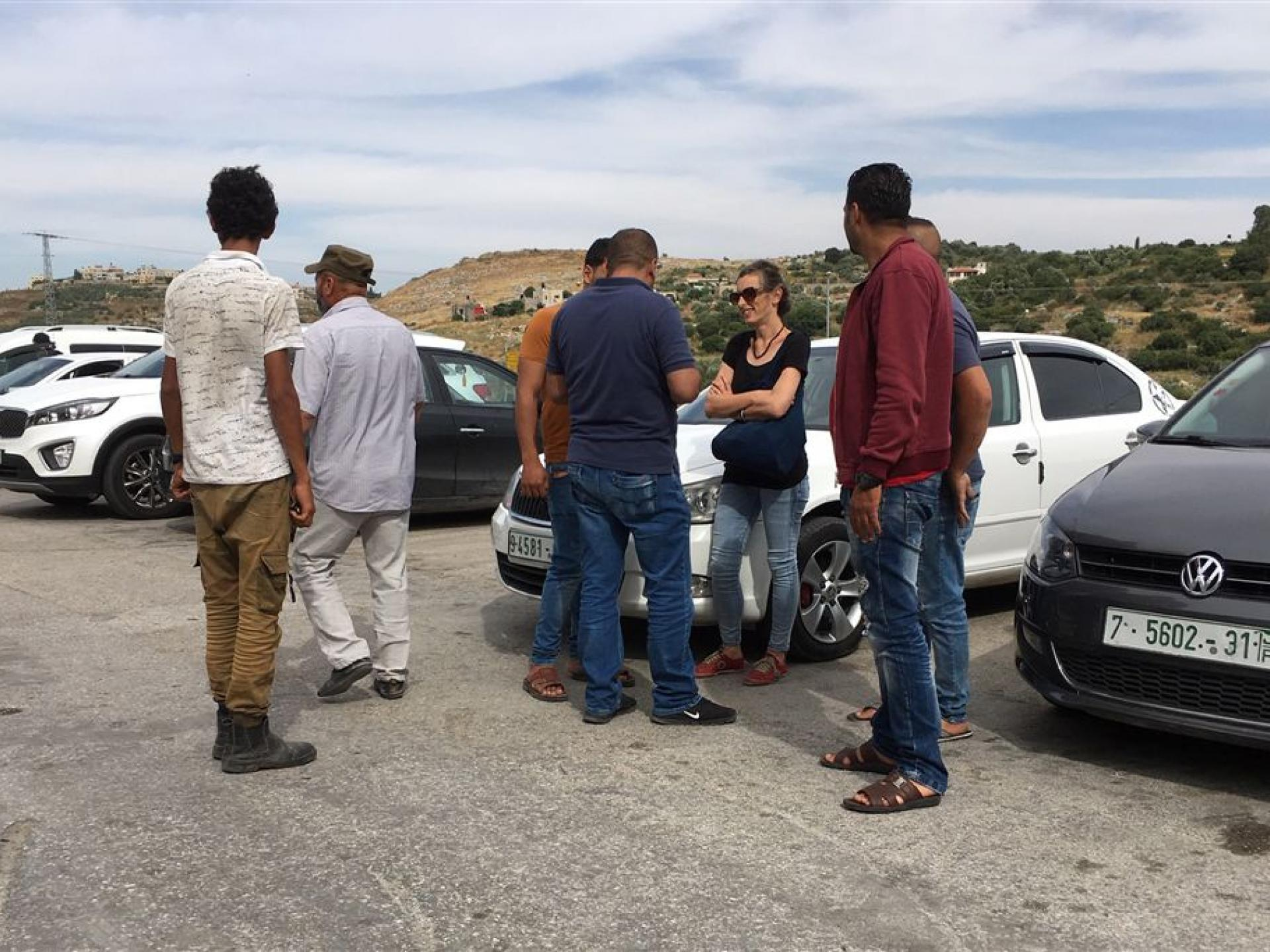 אישה באזור חניית מכוניות משוחחת עם מספר גברים