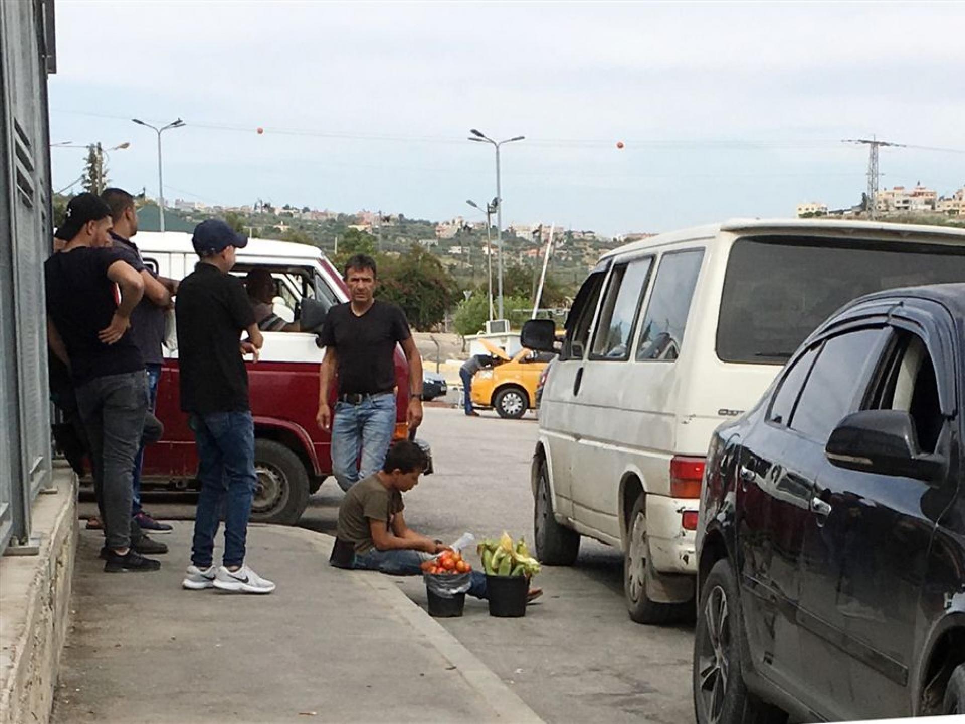 ילד, על שפת המדרכה בין מכוניות חונות מוכר דלי עם תירס ודלי עם עגבניות