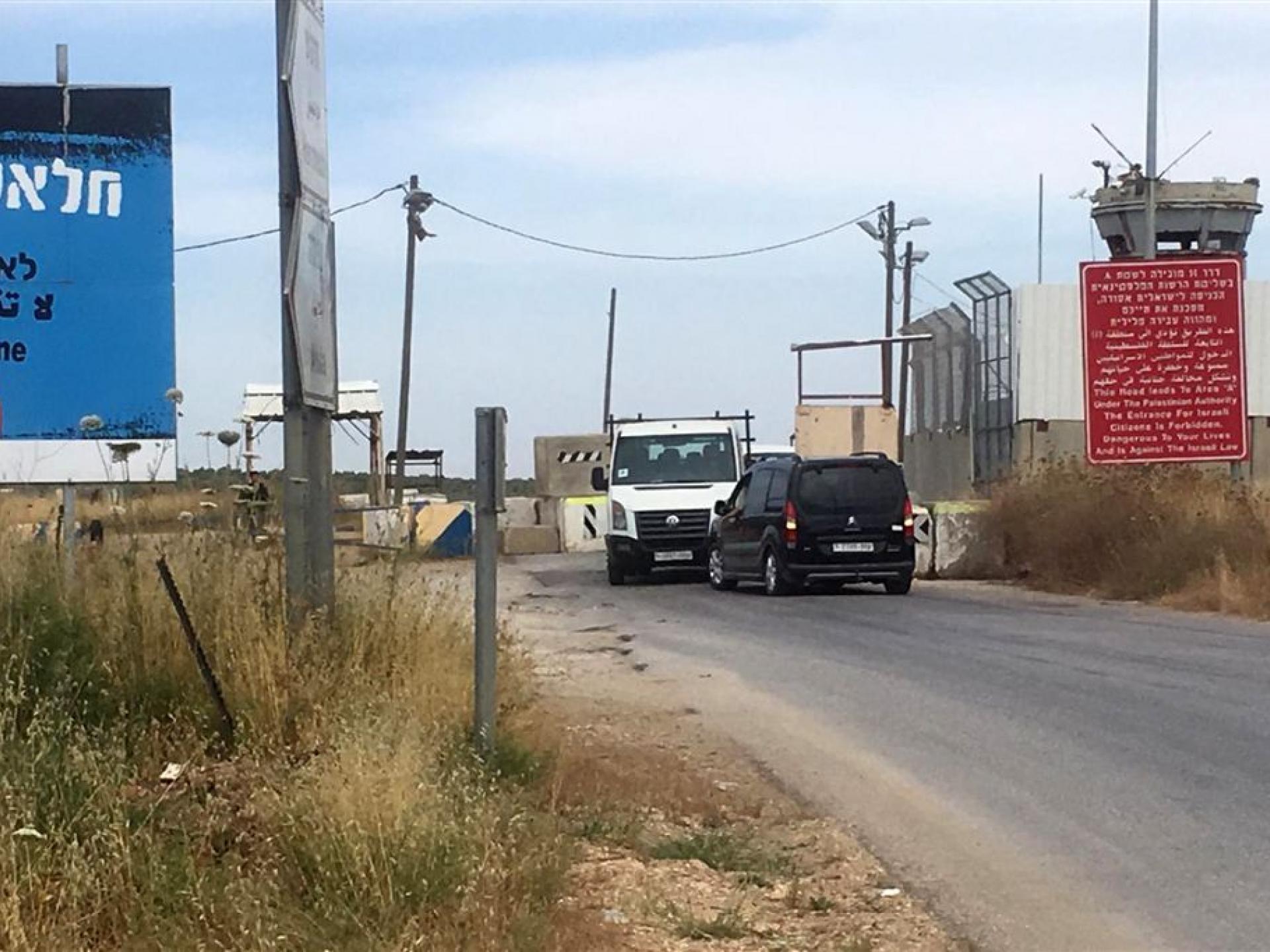 מכוניות תקעות לפני הבטונדות במחסום. לצידו הימני השלט האדום המכריז על סכנה לישראלים