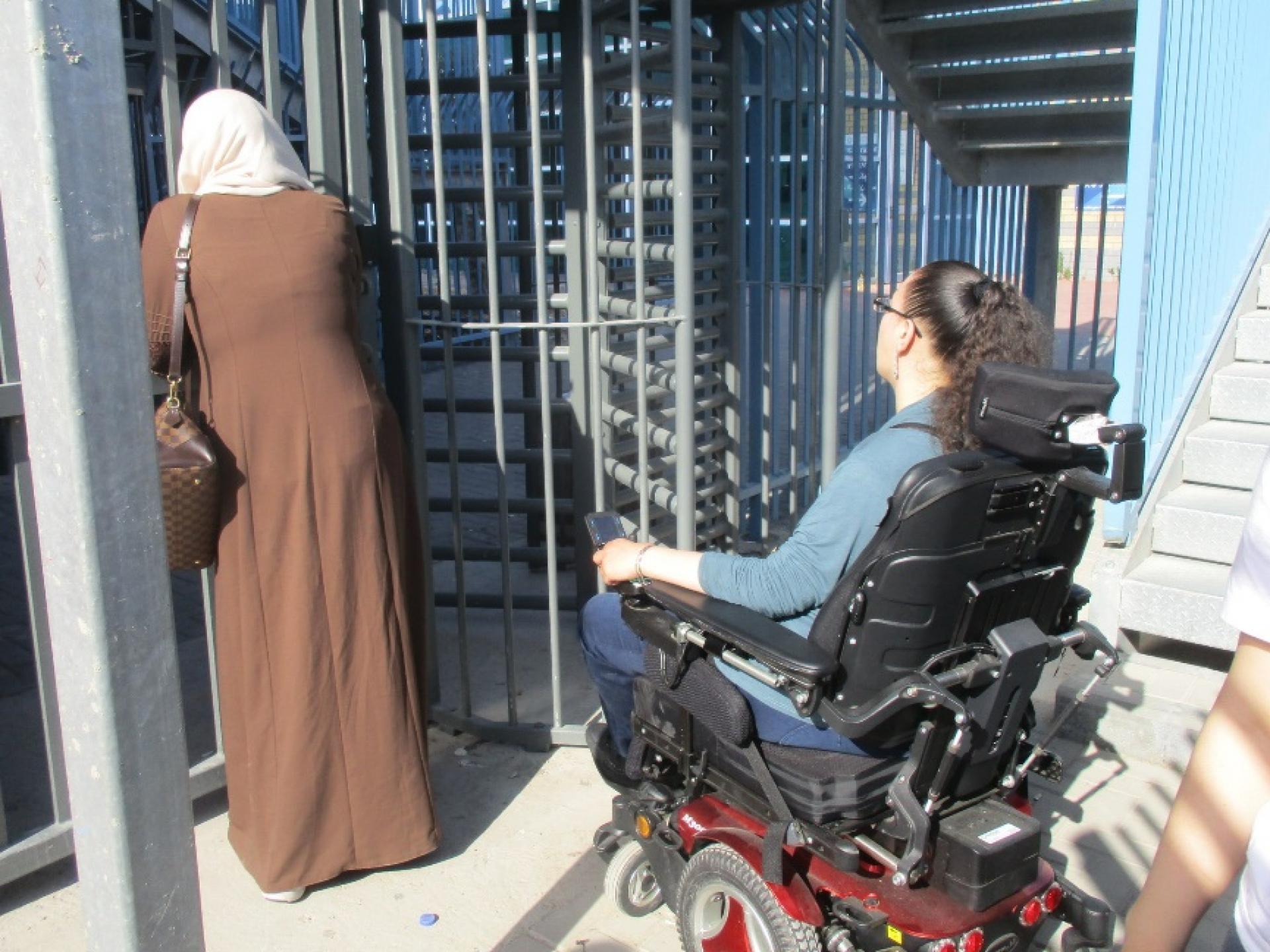 אמא ובתה הנכה לפני השער הסגור