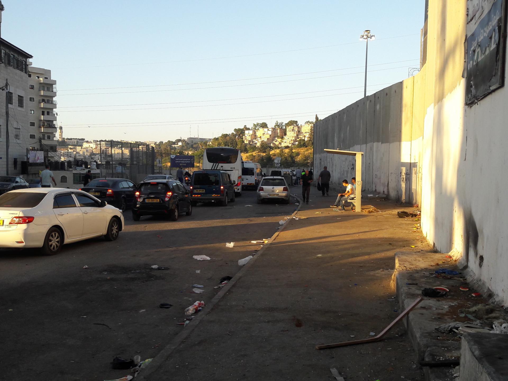 מחנה הפליטים שועפאט, מבט מהמחנה לעבר המחסום, מימין גדר ההפרדה. באופק רואים משמאל את המגדל של הר הצופים ולמרגלותיו עיסאוויה, ומימין את בתי צמרת הבירה במורדות הגבעה הצרפתית