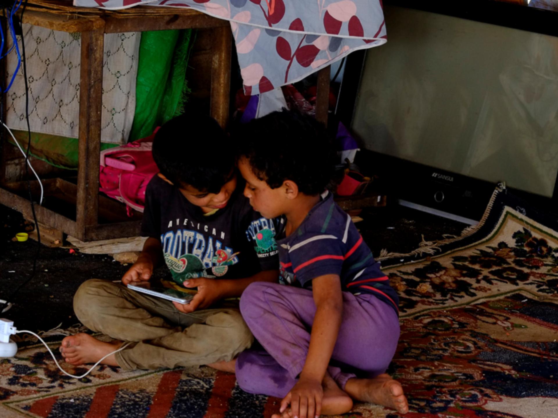 בצילום רואים שניים מילדי המשפחה שקועים במשחק בטבלט
