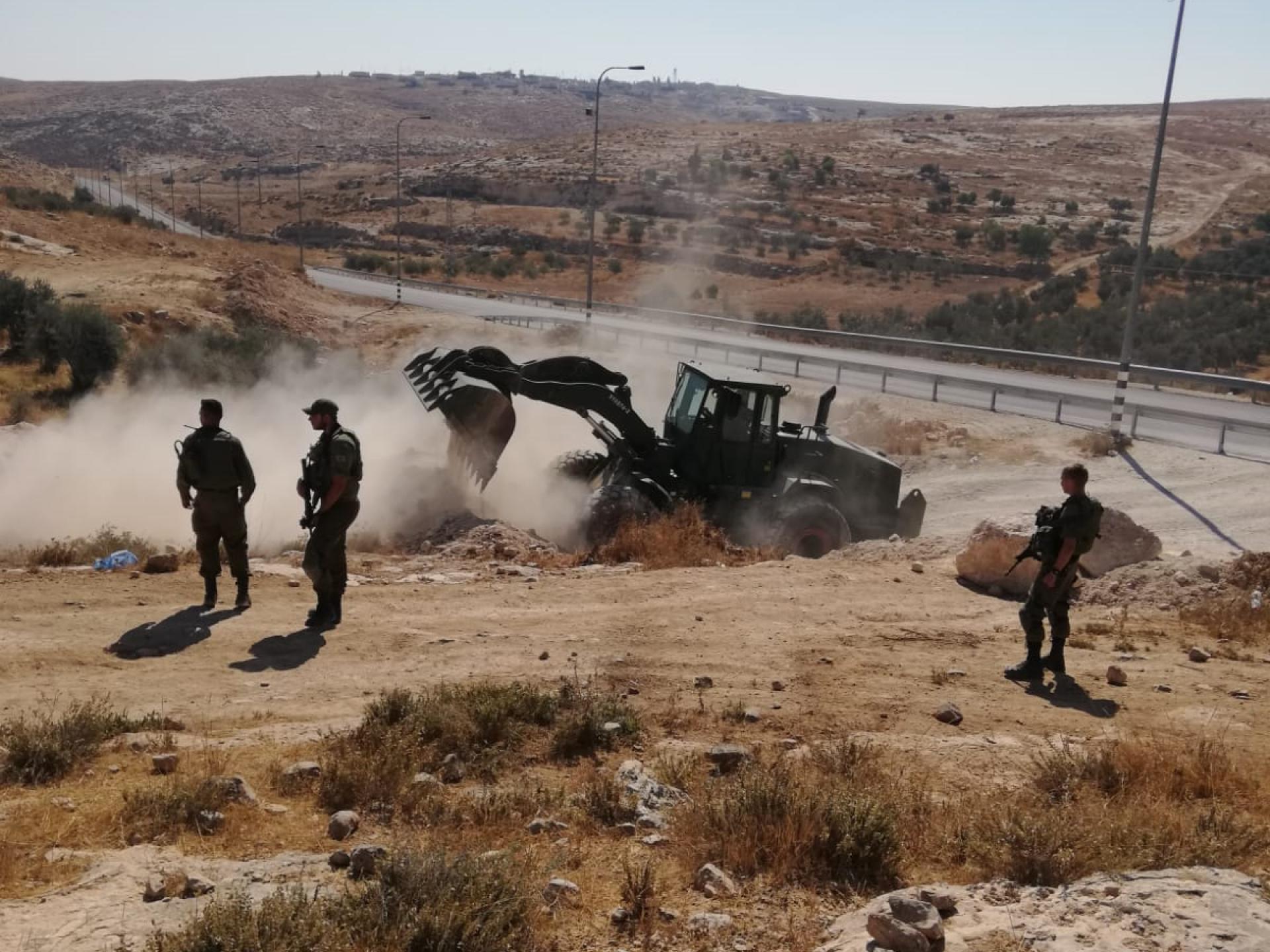 טרקטור חופר באמצע הדרך וחיילים סביבו
