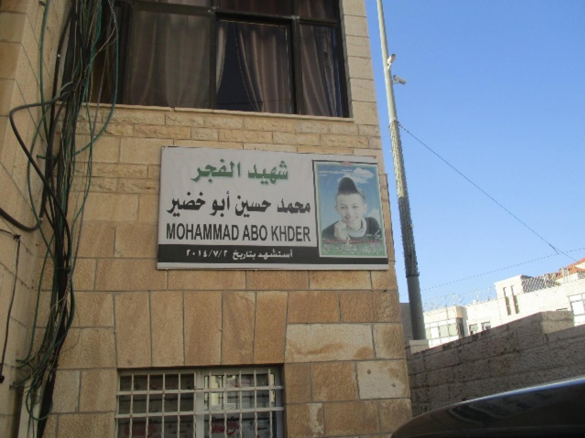 שלט קטן עם תמונת הילד הרצוח, מוחמד אבו-ח'דיר