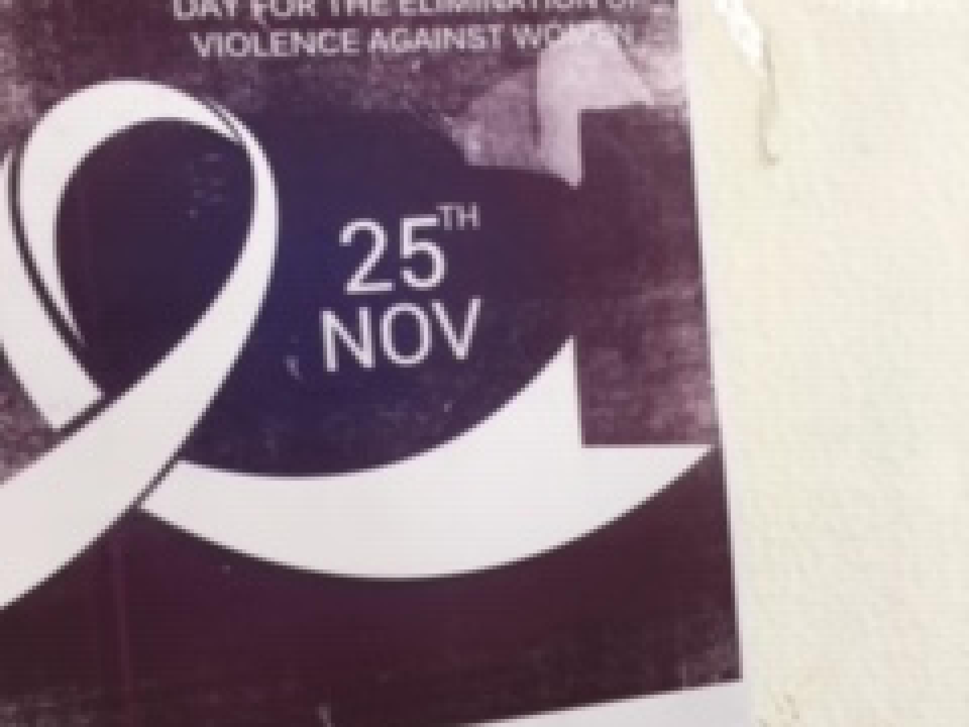 """פוסטר על הקיר: """"יום בינלאומי למיגור אלימות נגד נשים."""""""