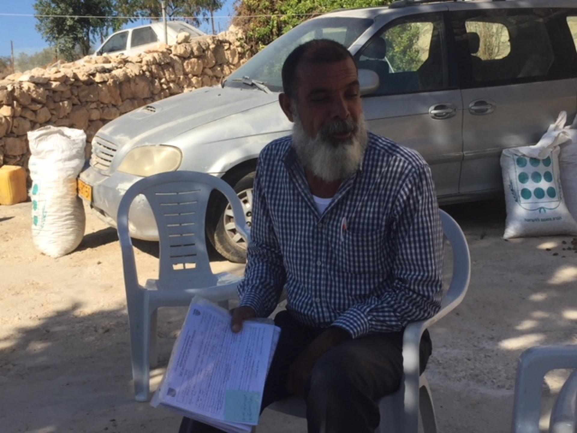 אדם יושב ליד המכונית בחצר ובידו מסמכים