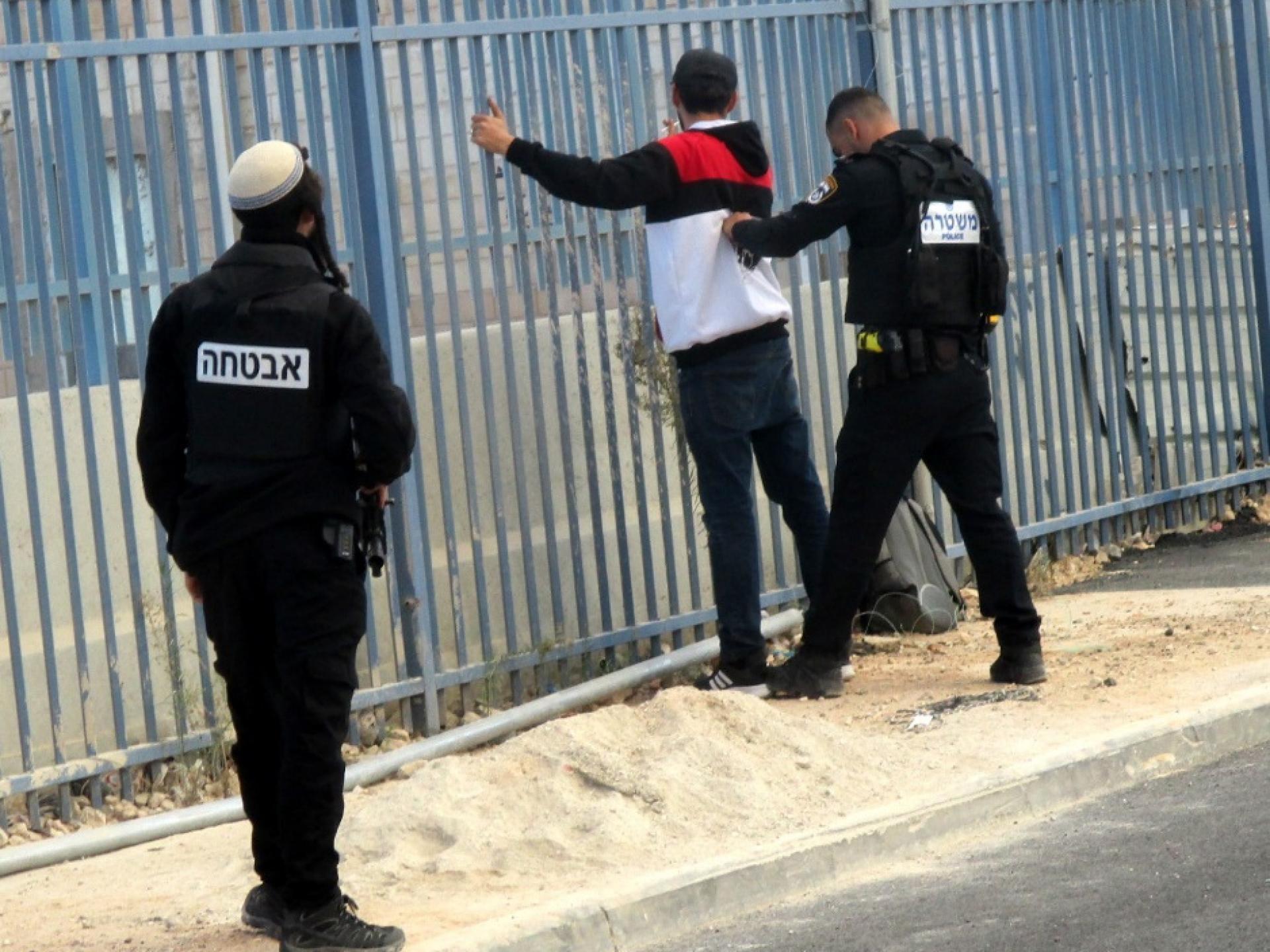 שוטר בודק צעיר פלסטיני