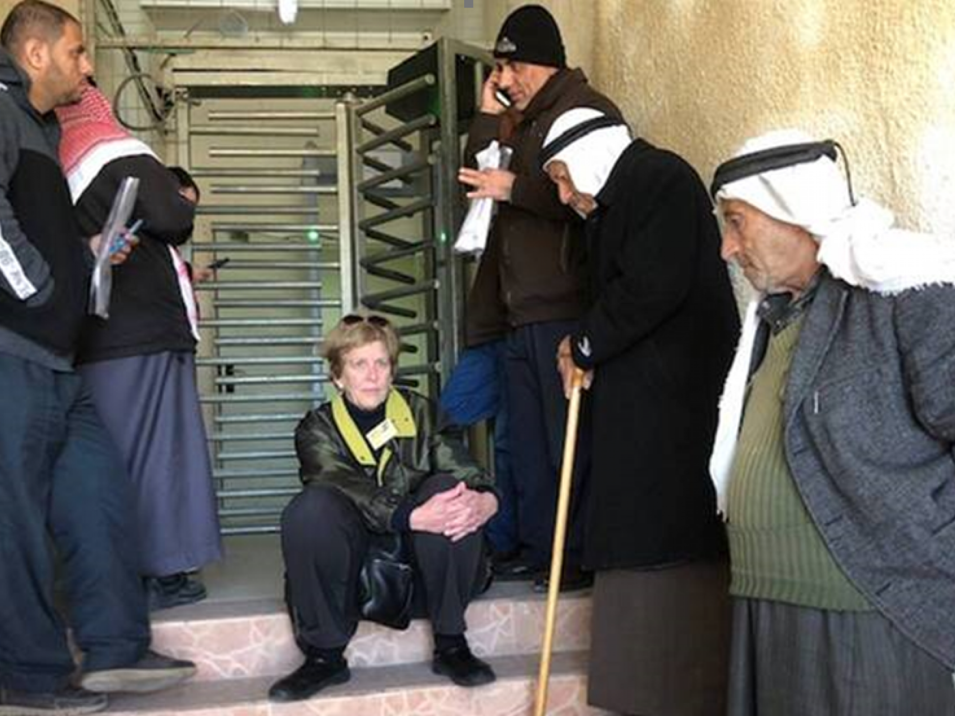 אישה יושבת ליד קרוסלה ומספר גברים פלסטינים לידה