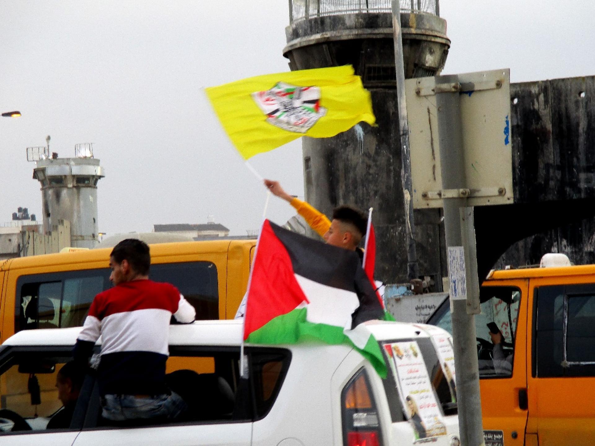 שיירת רכבים דוהרת בצהלות ונפנופי דגלים לכבוד מישהו שיצא מהכלא