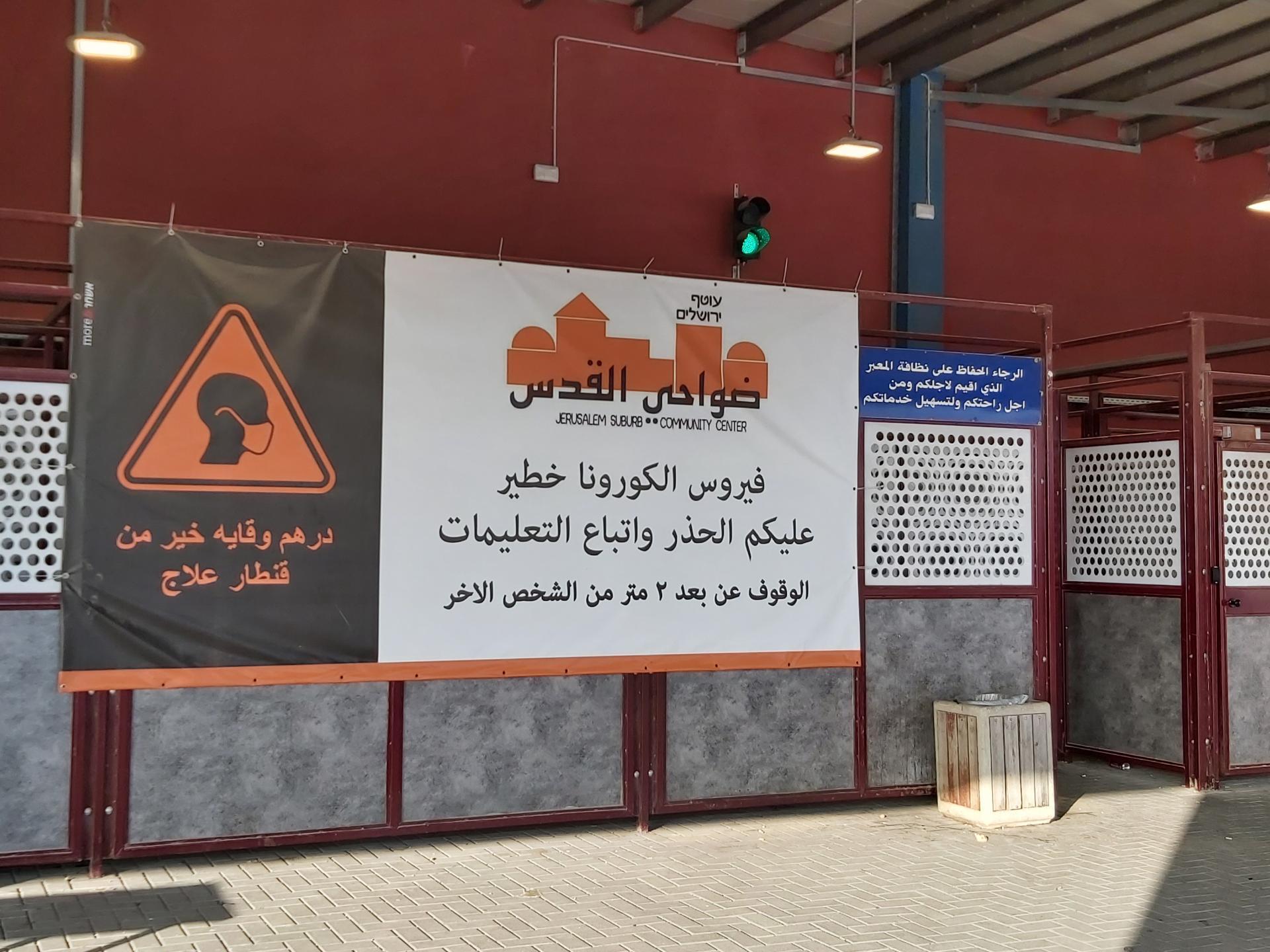 שלט המזהיר מהקורונה בכניה למחסום