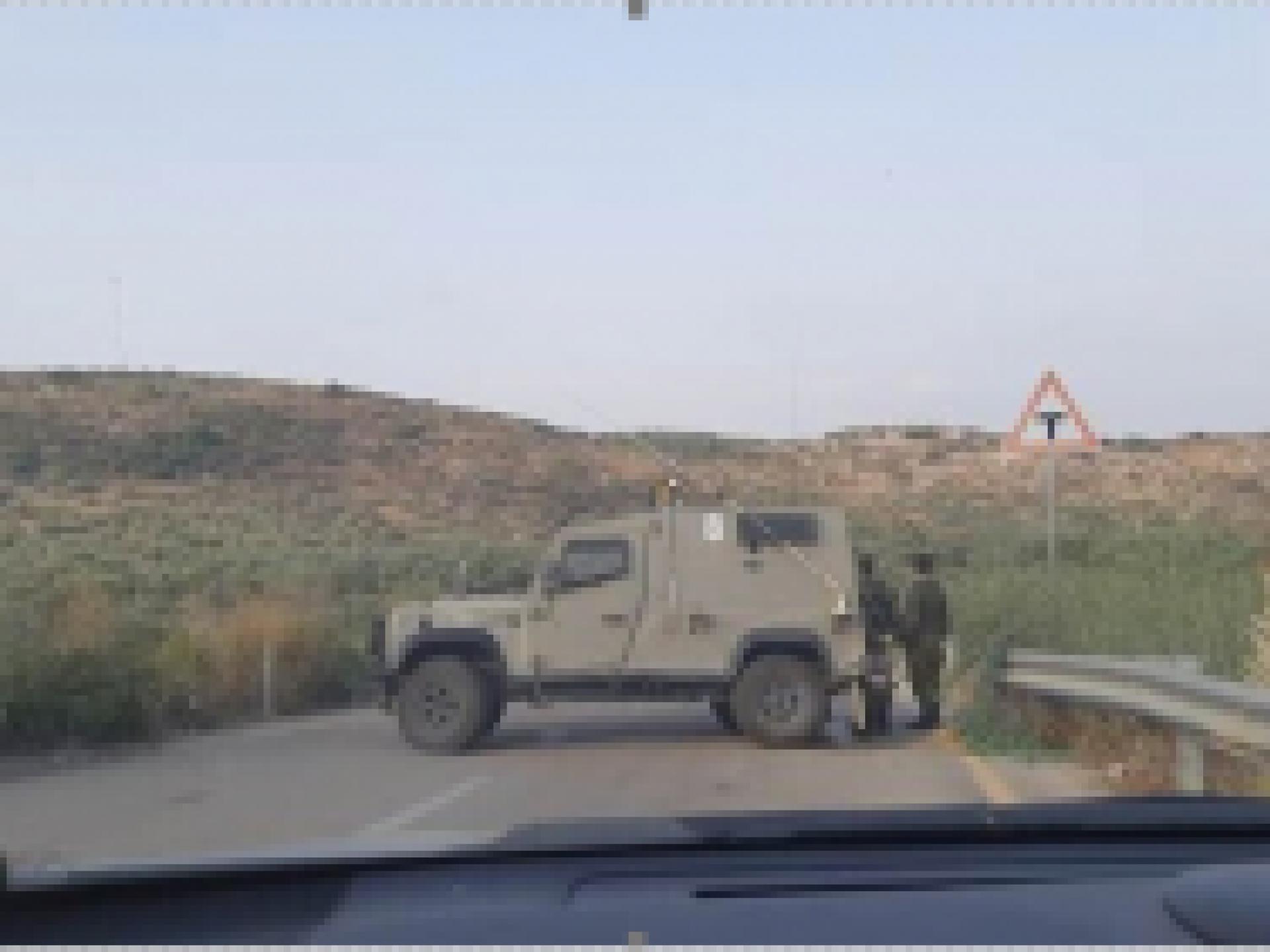 רכב צבאי לרוחב הכביש ושני חיילים