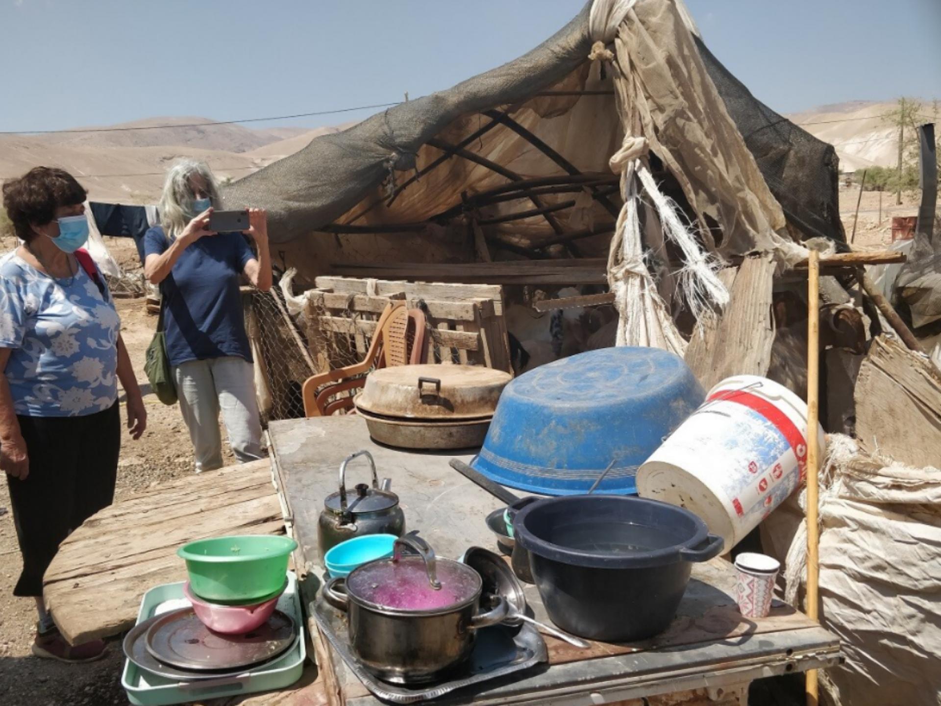כלי מטבח ליד ההריסות והצללה מאולתרת