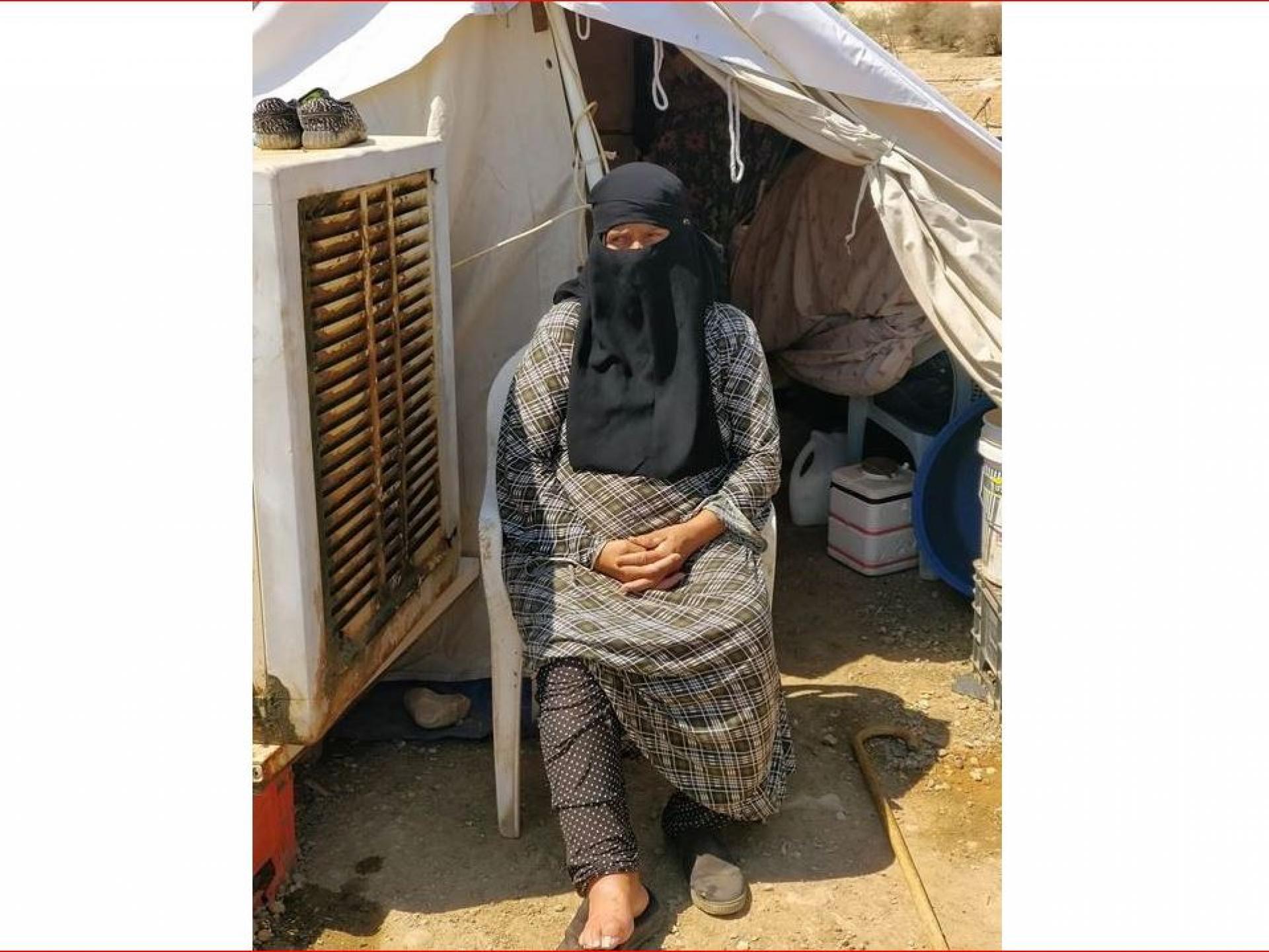 אישה יושבת בפתח אוהל מאולתר
