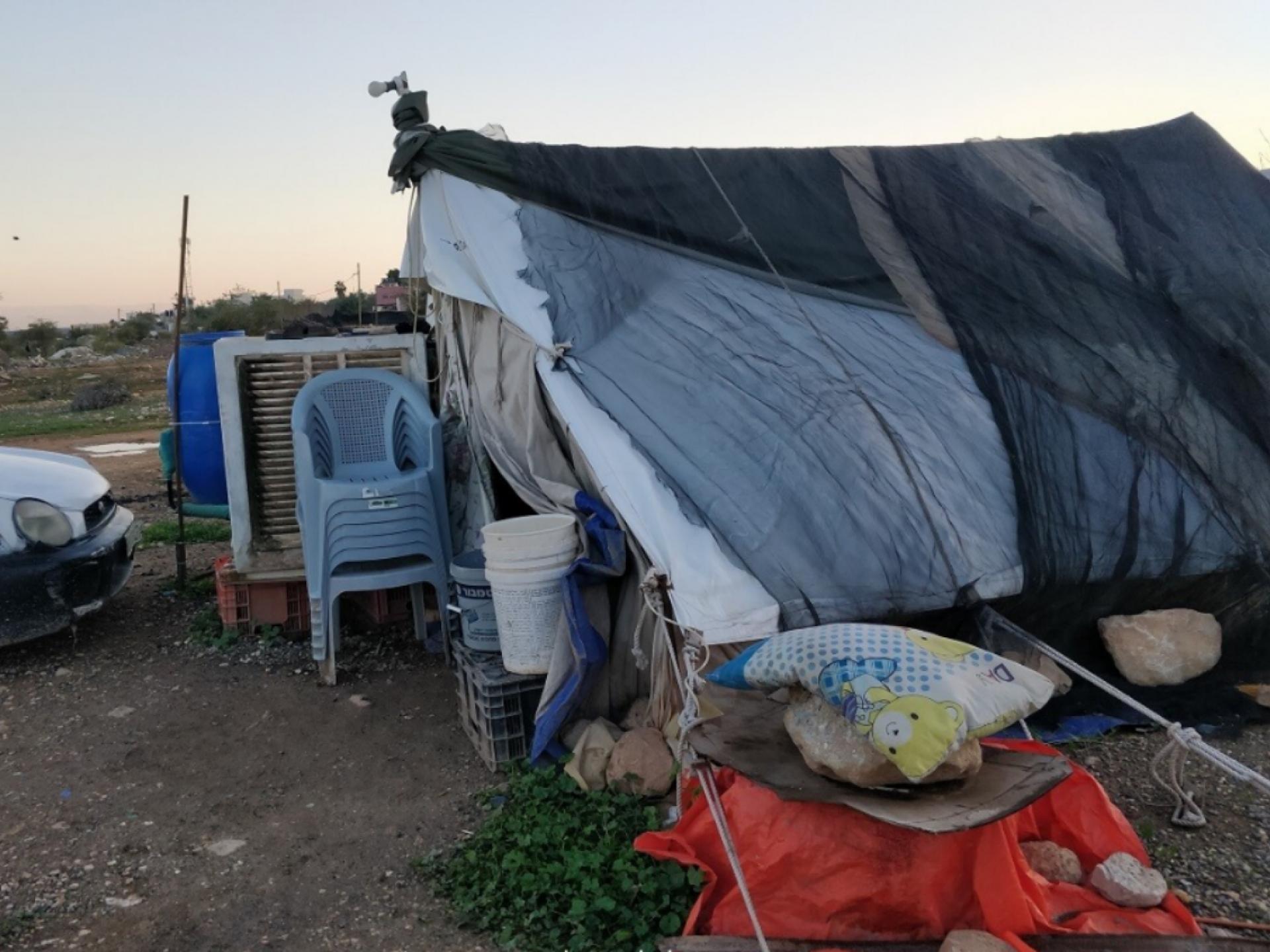 רואים אוהל עשוי מטלאים של ניילונים ושמיכות קרועות