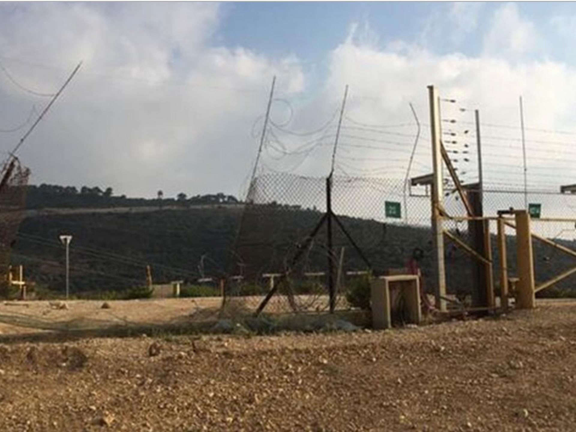רואים שער צהוב נעול באמצע המחסום ולידו פִרצה גדולה בגדר