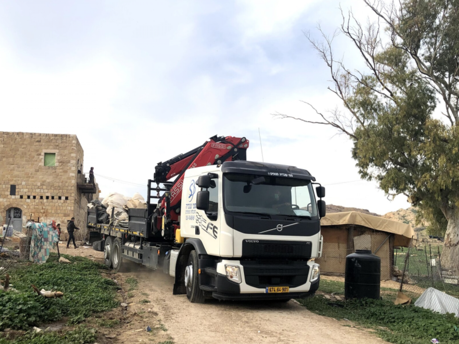 A large truck near residets' stone houses
