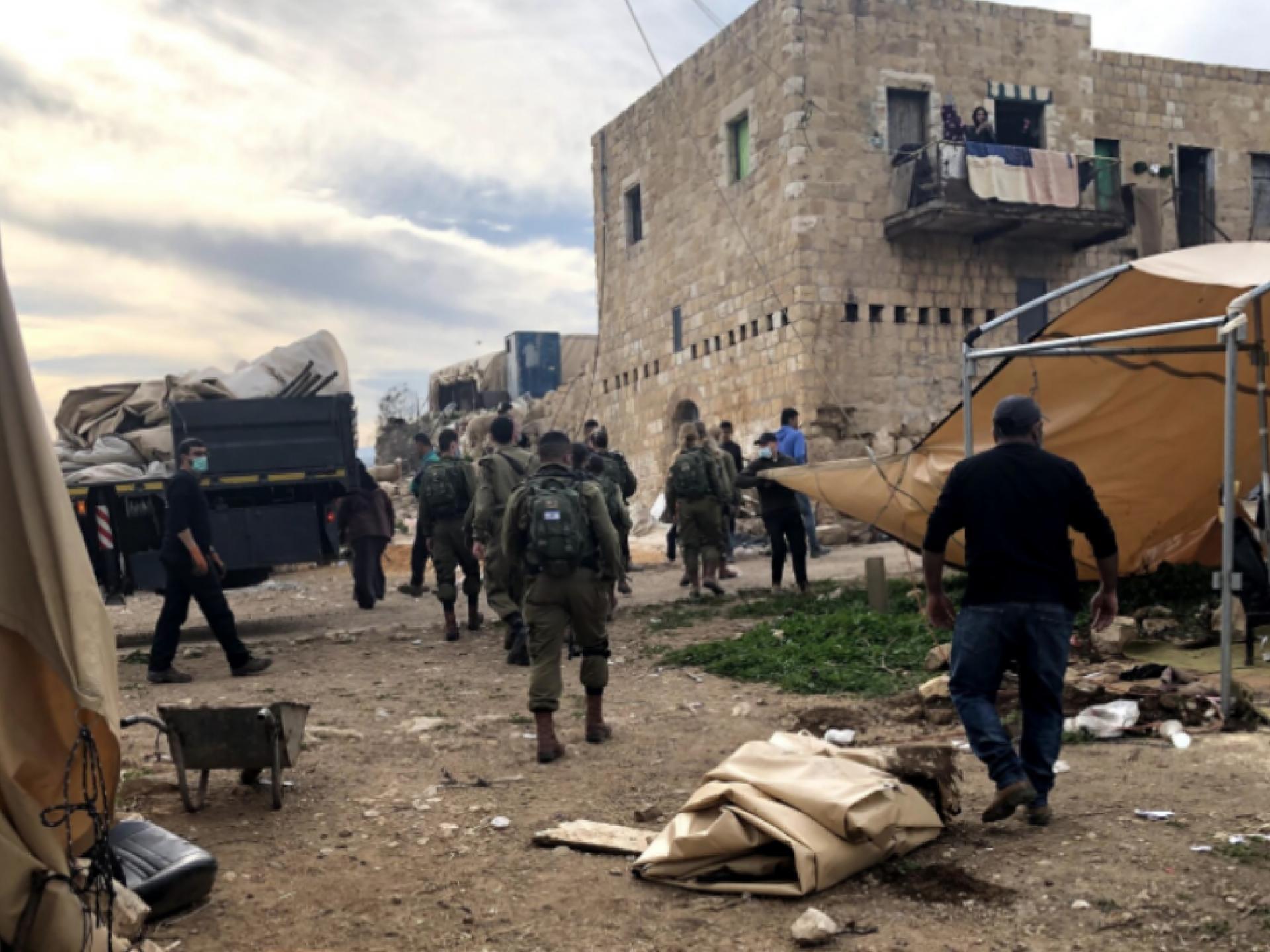 חיילים מסתובביפ בחצר של הפלסטינים ומפרקים סככה לכבשים