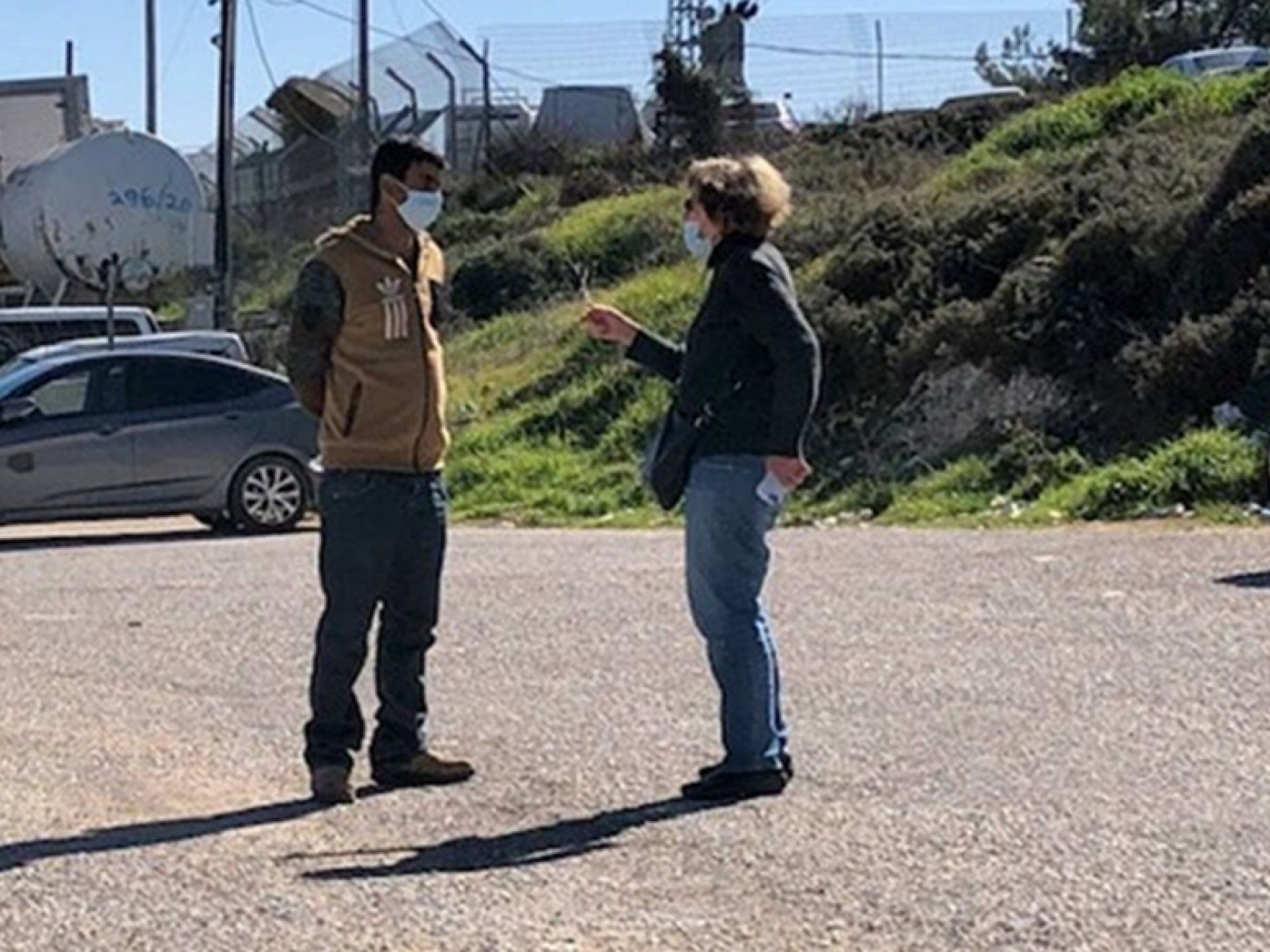 אישה משוחחת עם פלסטיני בחניון