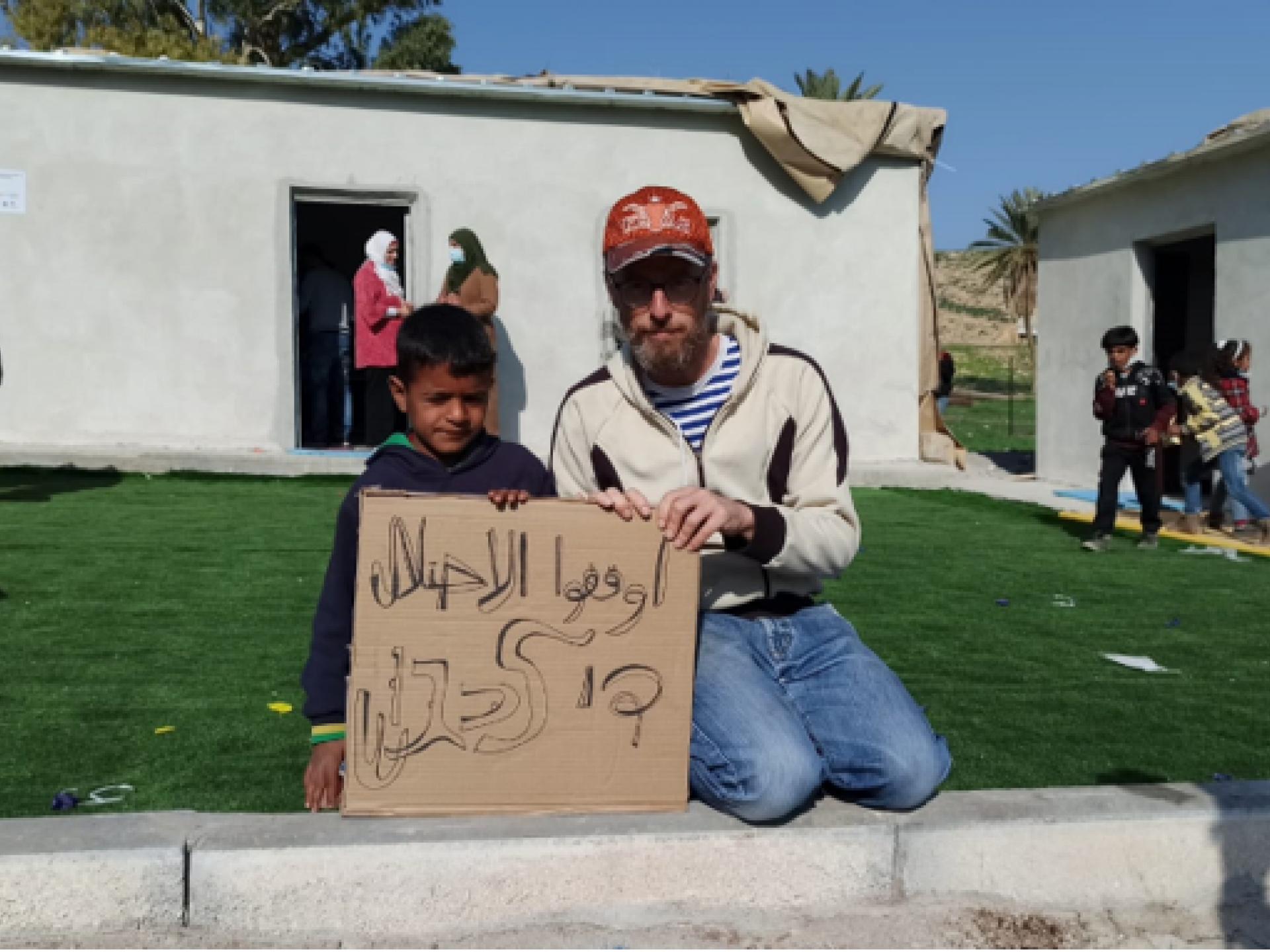 פעיל שלום ותלמיד מחזיקים שט ועליו כתוב בעברית ובערבעת: די כיבוש