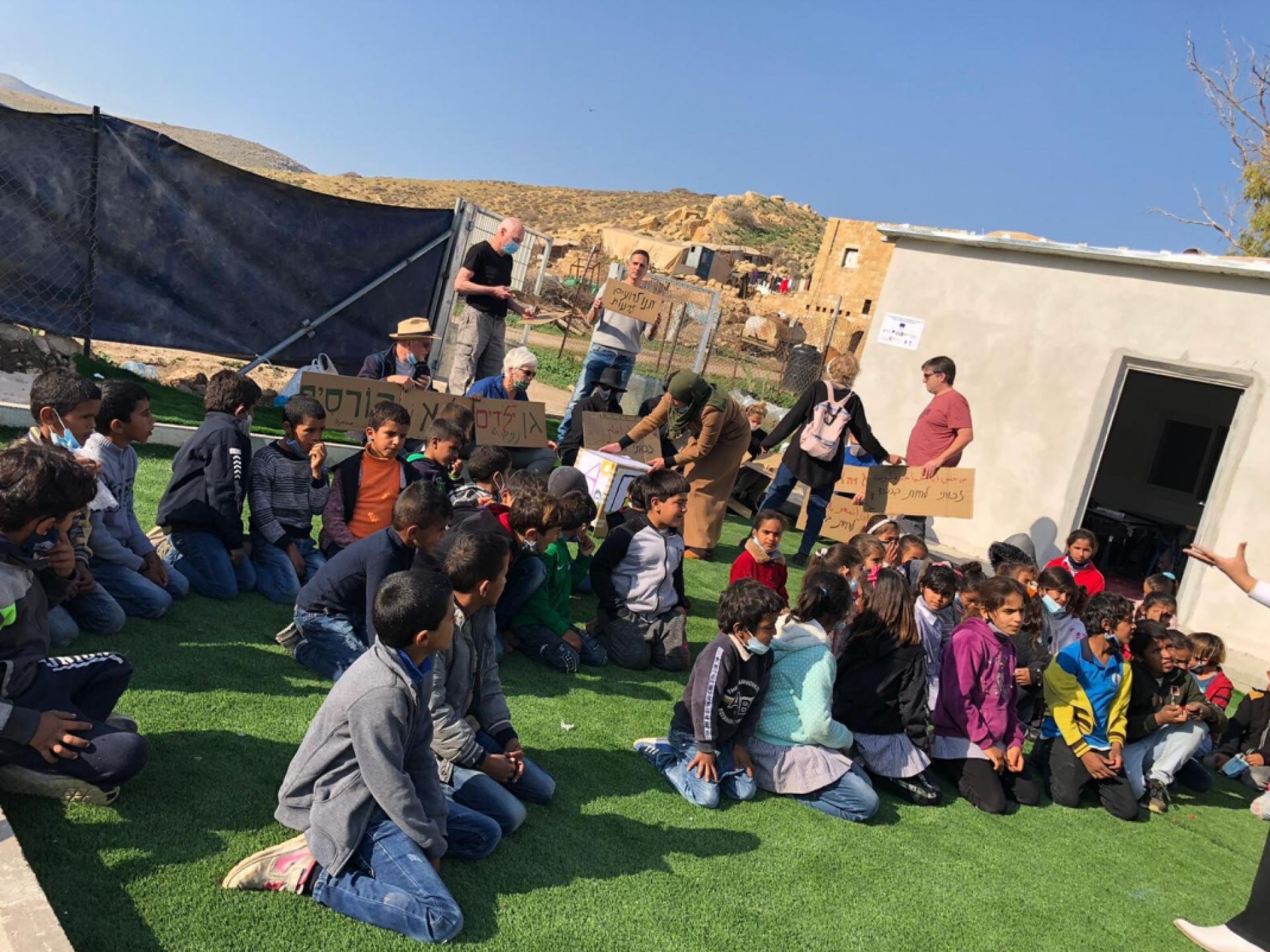 בחצר קטנה של בית הספר יושבים תלמידים, מורים ופעילי שלום