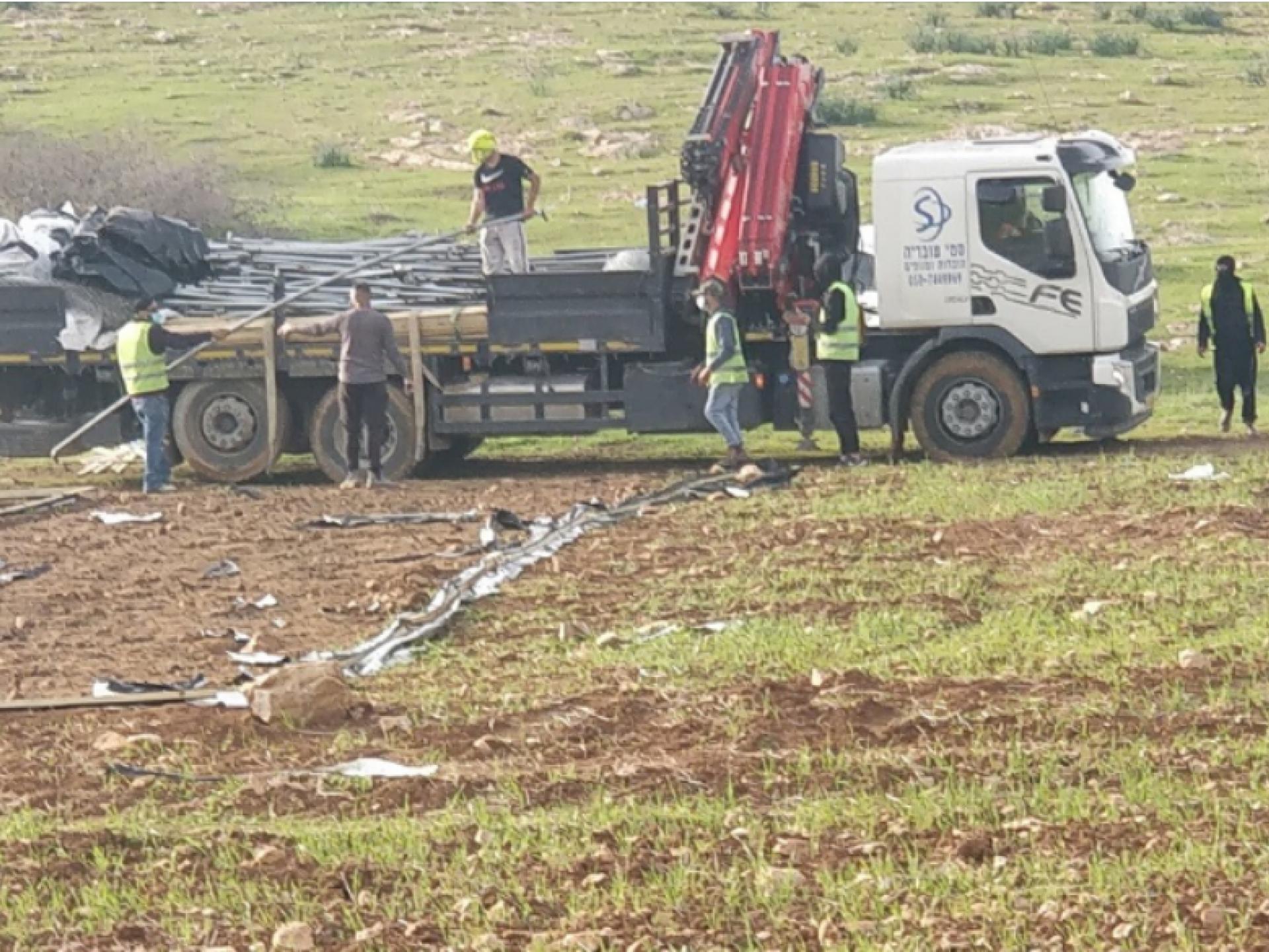 משאית מנוף עומדת בשטח הפתוח, אנשי המינהל האזרחי מעמיסים עליה ציוד של המאהל הפלסטיני שנלקח מהם