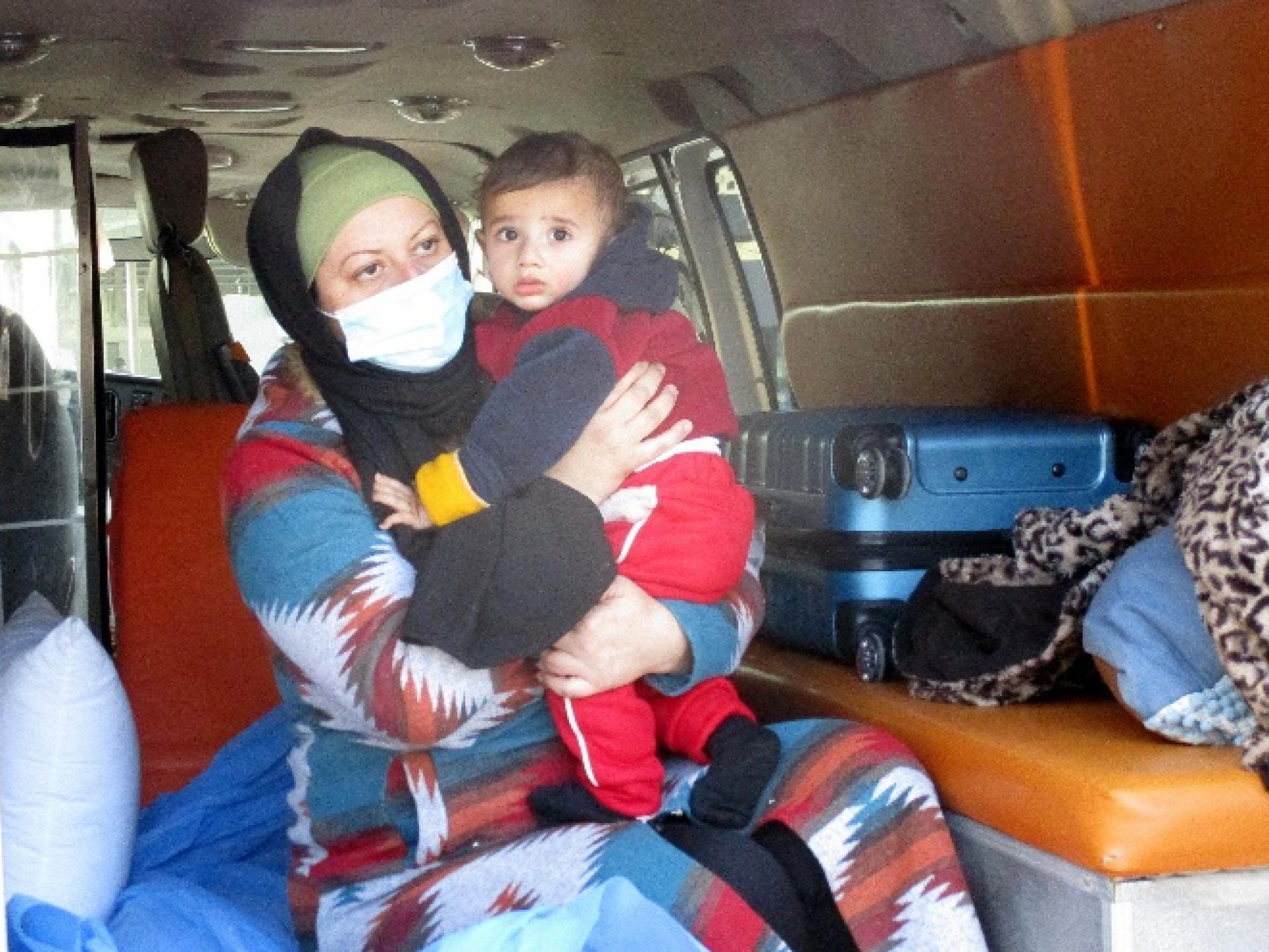 פוראת, תינוק בן 11 חודש, חולה בסרטן בזרועות אמו בתוך האמבולנס