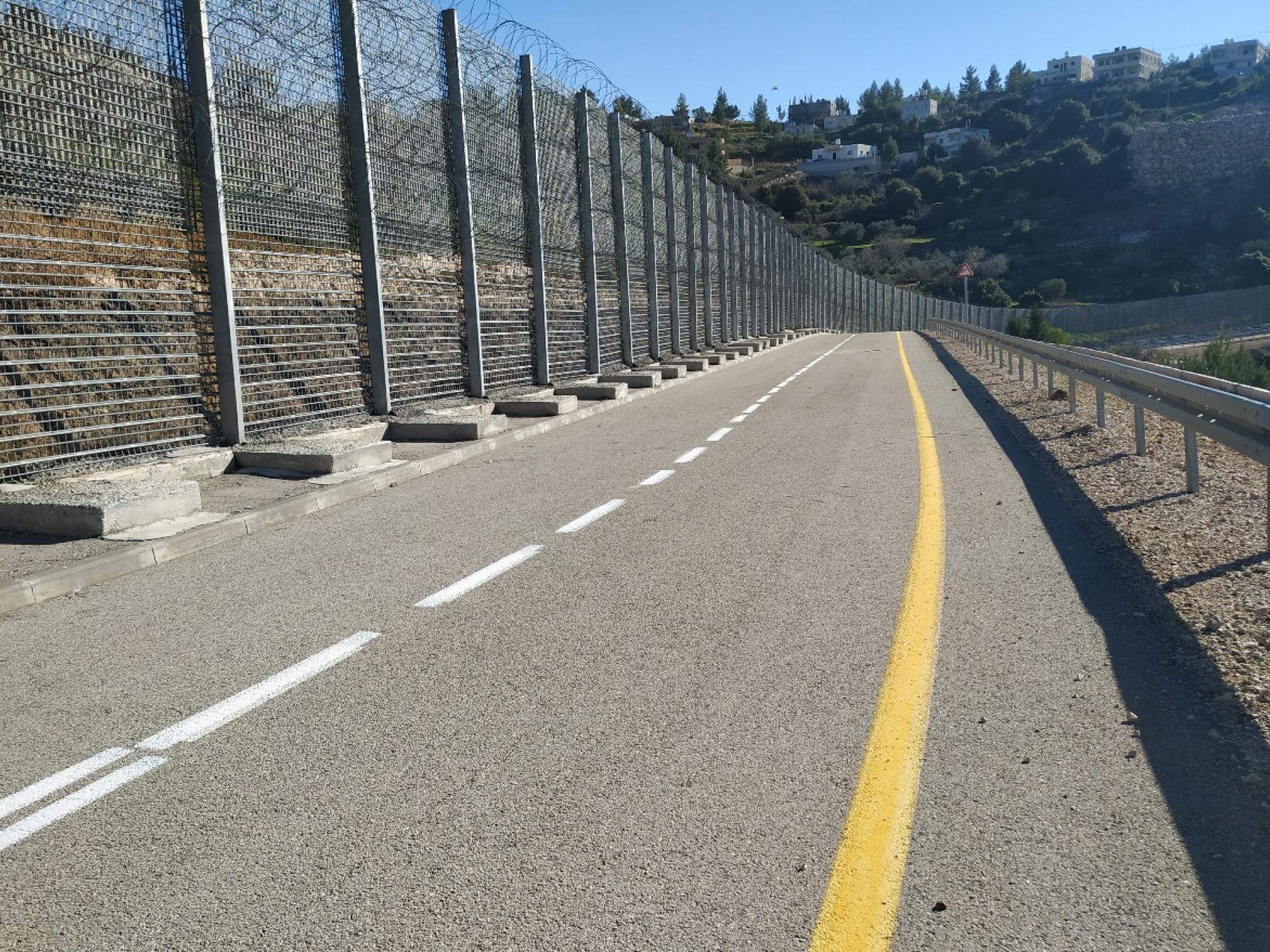החומה המפרידה בין בתי הכפר ואלאג'ה לאדמות החקלאיות והמעינות שלו.