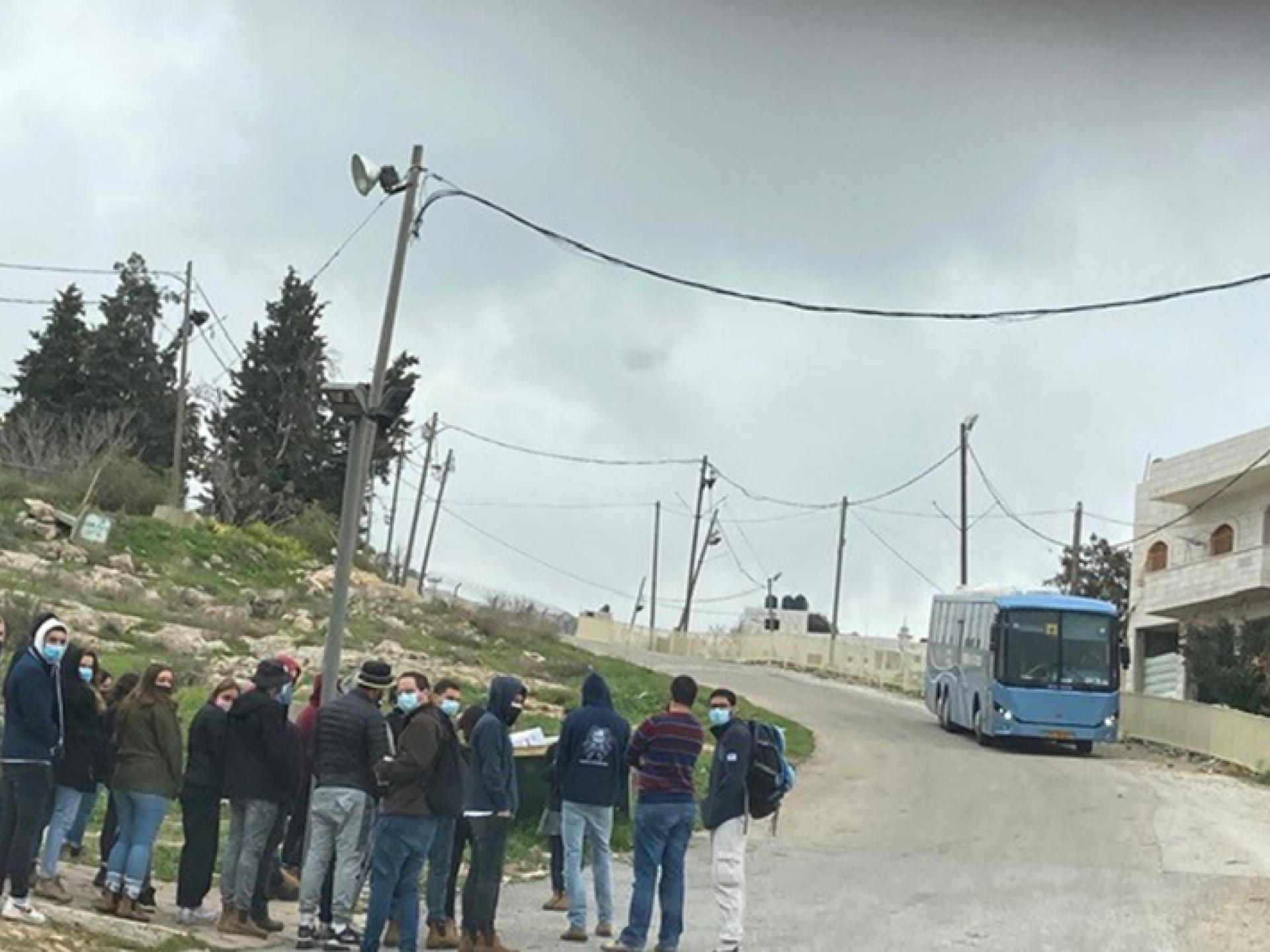 קבוצת תלמידים עומדיל על כביש ומקבלים הסברים