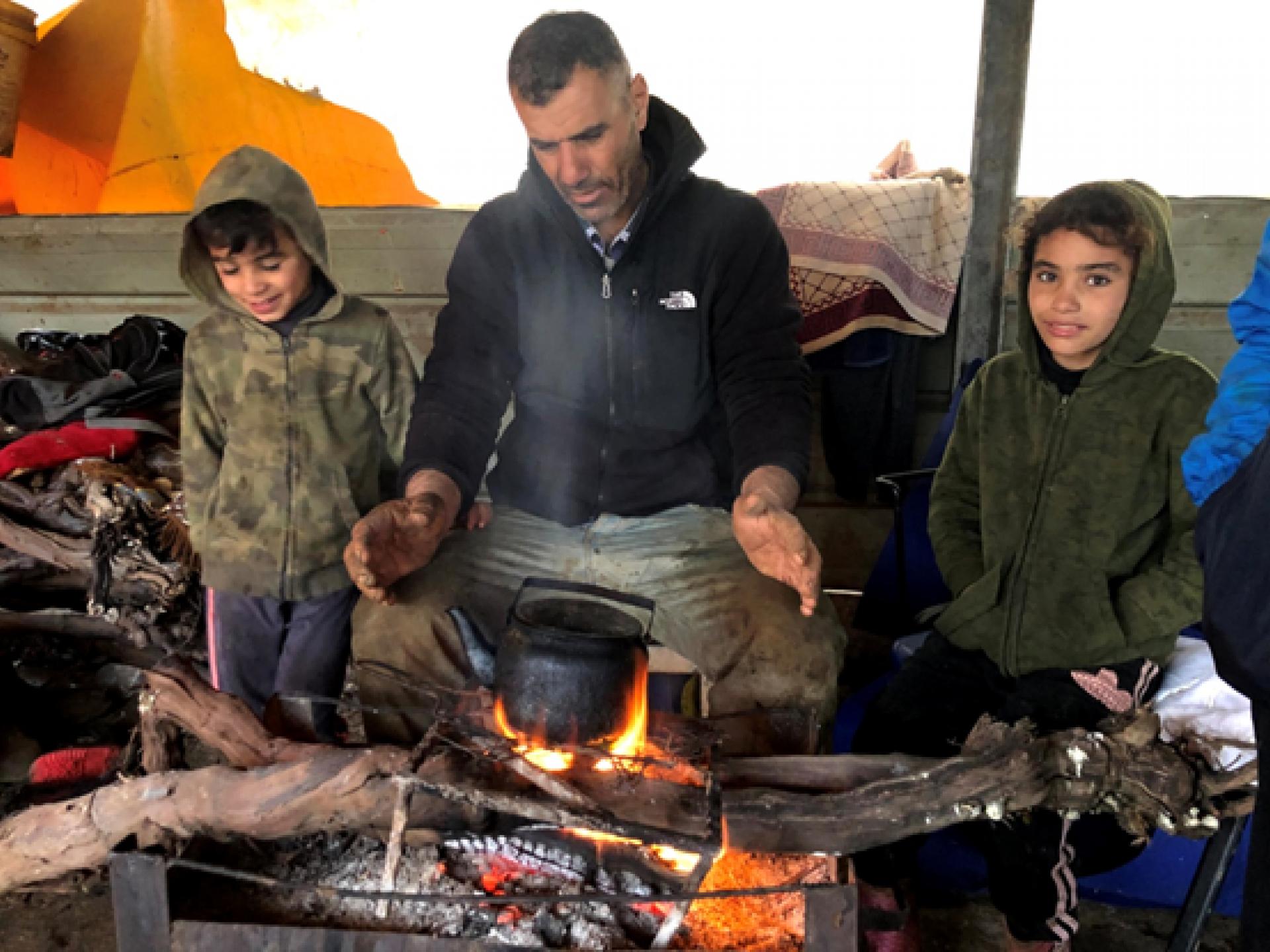 אב וילדיו מתחממים בתוך האוהל ליד תנור של גחלים בוערות