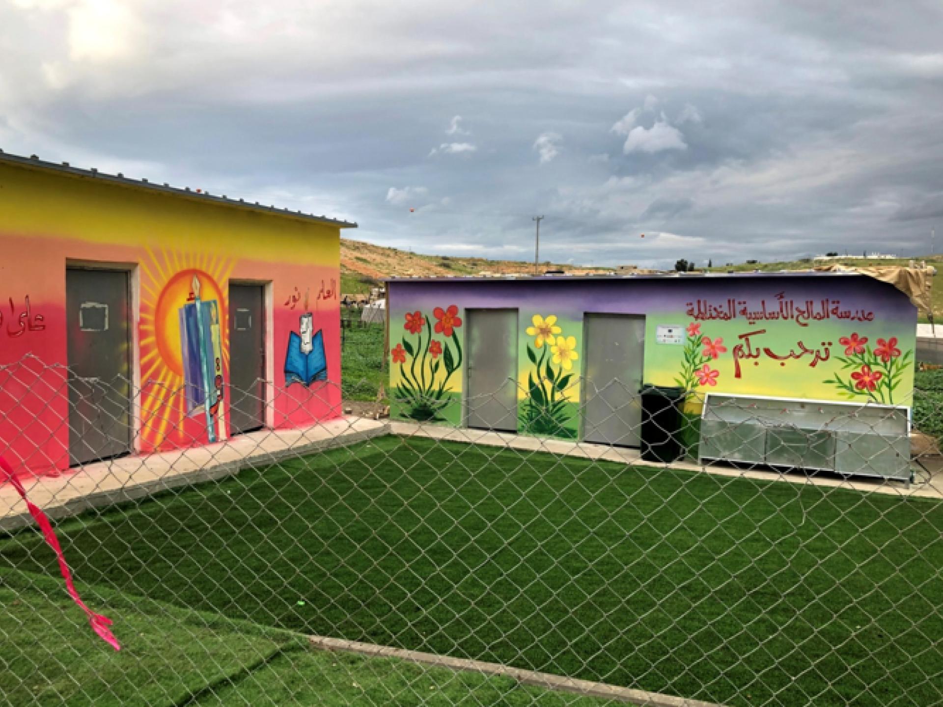 שני מבנים קטנים של בית ספר, דשא מפלסטיק ירוק מאוד וציורי קיר יפים