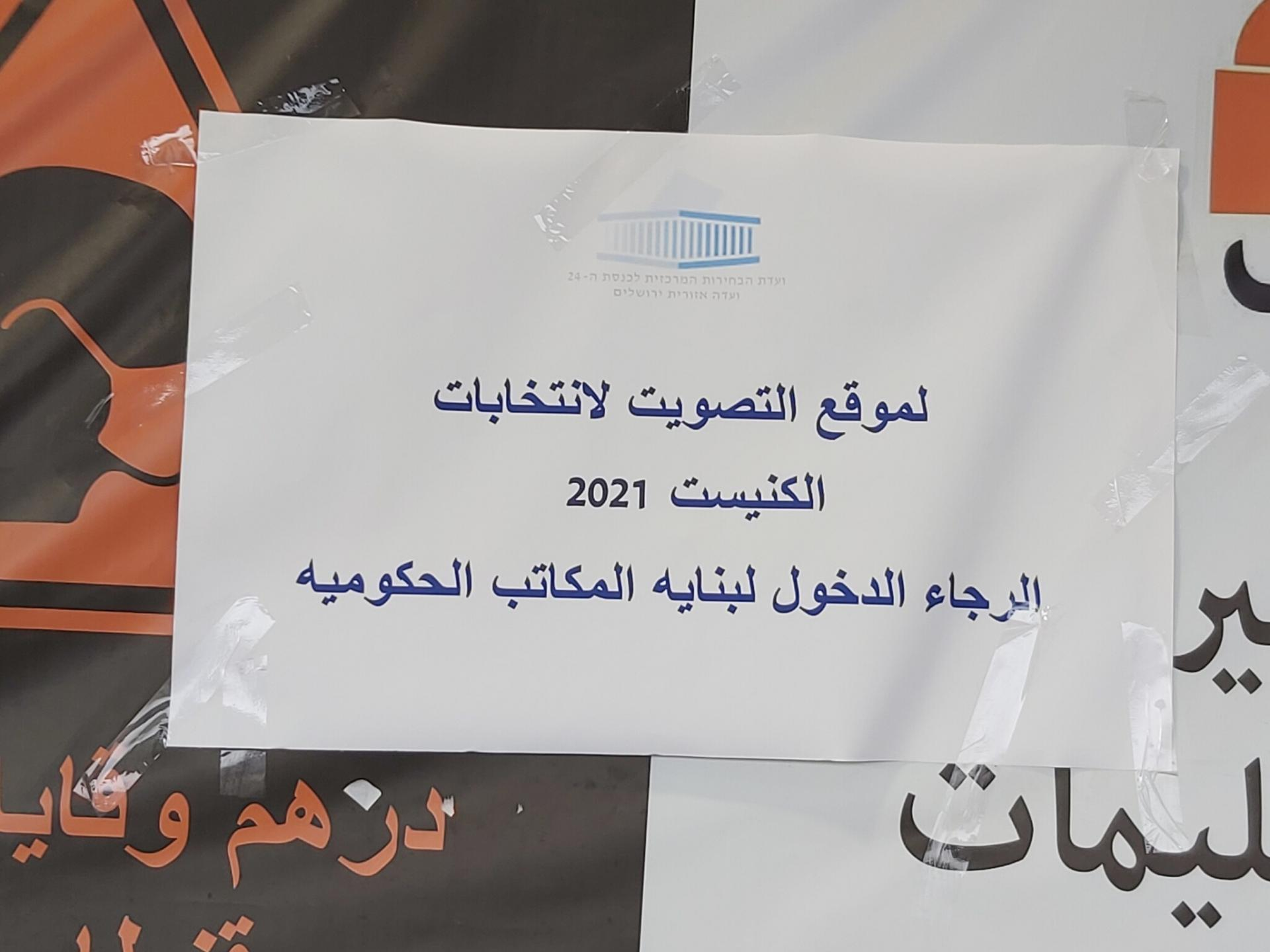 שלט נייר עליו כתוב: לאתר ההצבעה לבחירות/ הכנסת 2021/ אנא הכנס לבניין משרדי הממשלה