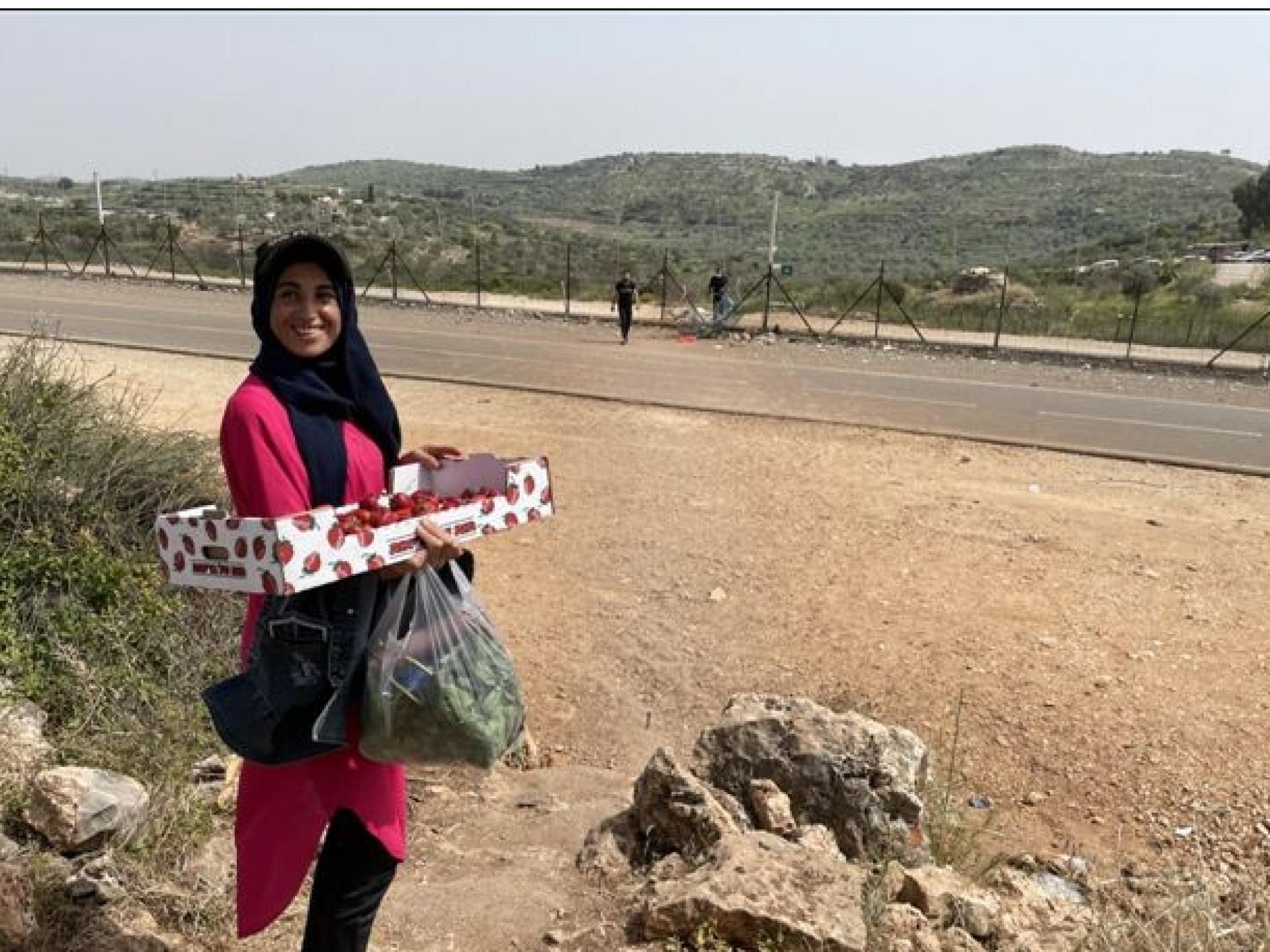 אשה עם קרטון תותים בידיה ליד פרצה בגדר ההפרדה