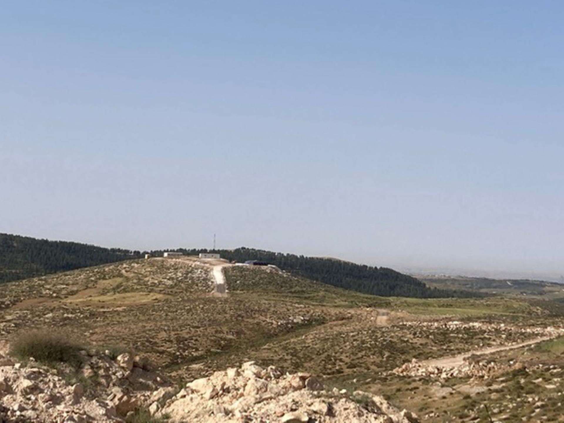 בראש הגבעה רואים מבנים אחדים, חוות צאן פיראטית של מתנחלים